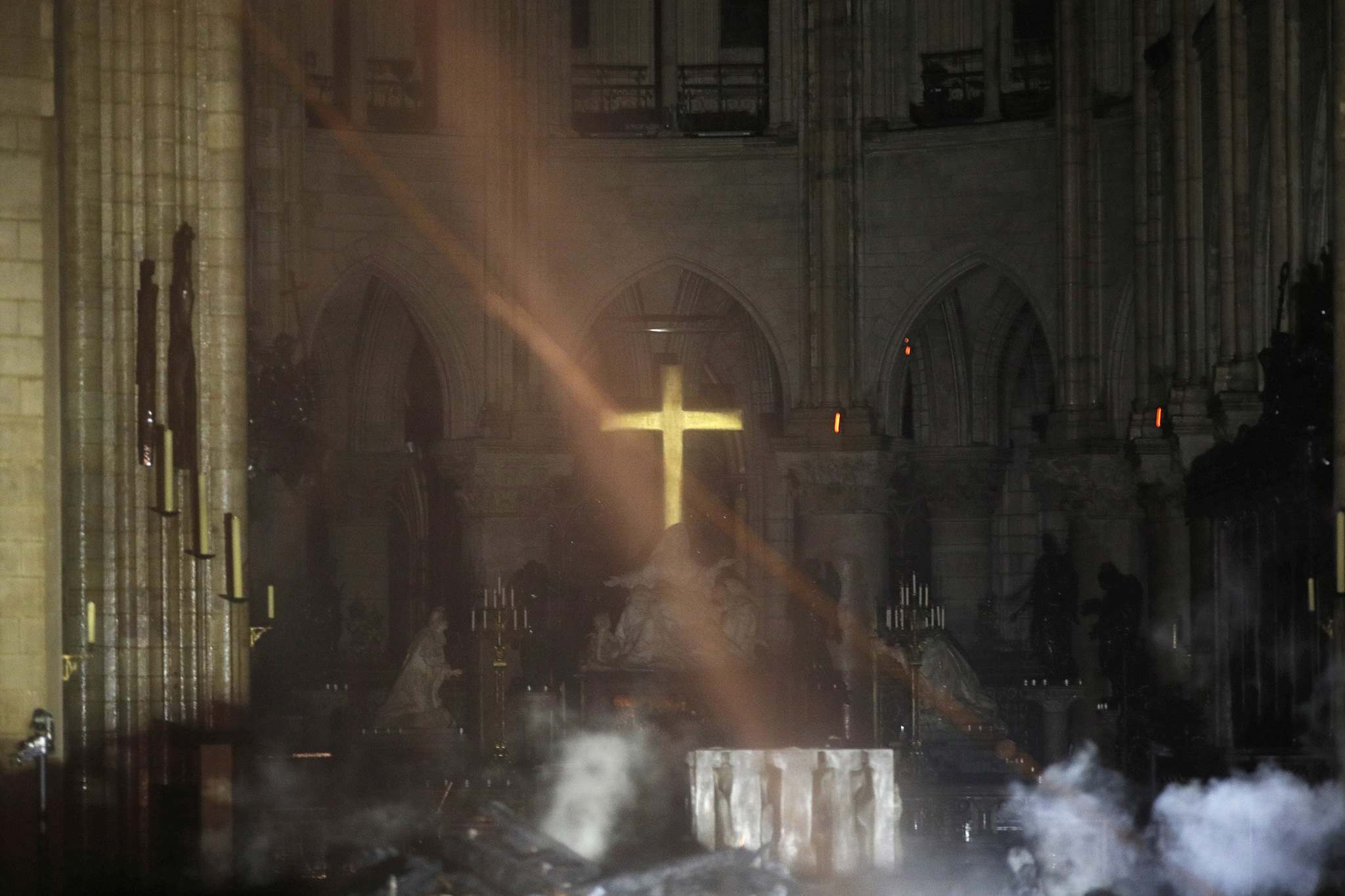 Philippe Wojazer / Pool</p><p>Smoke is seen around the altar inside Notre Dame Cathedral in Paris on Monday.</p></p>