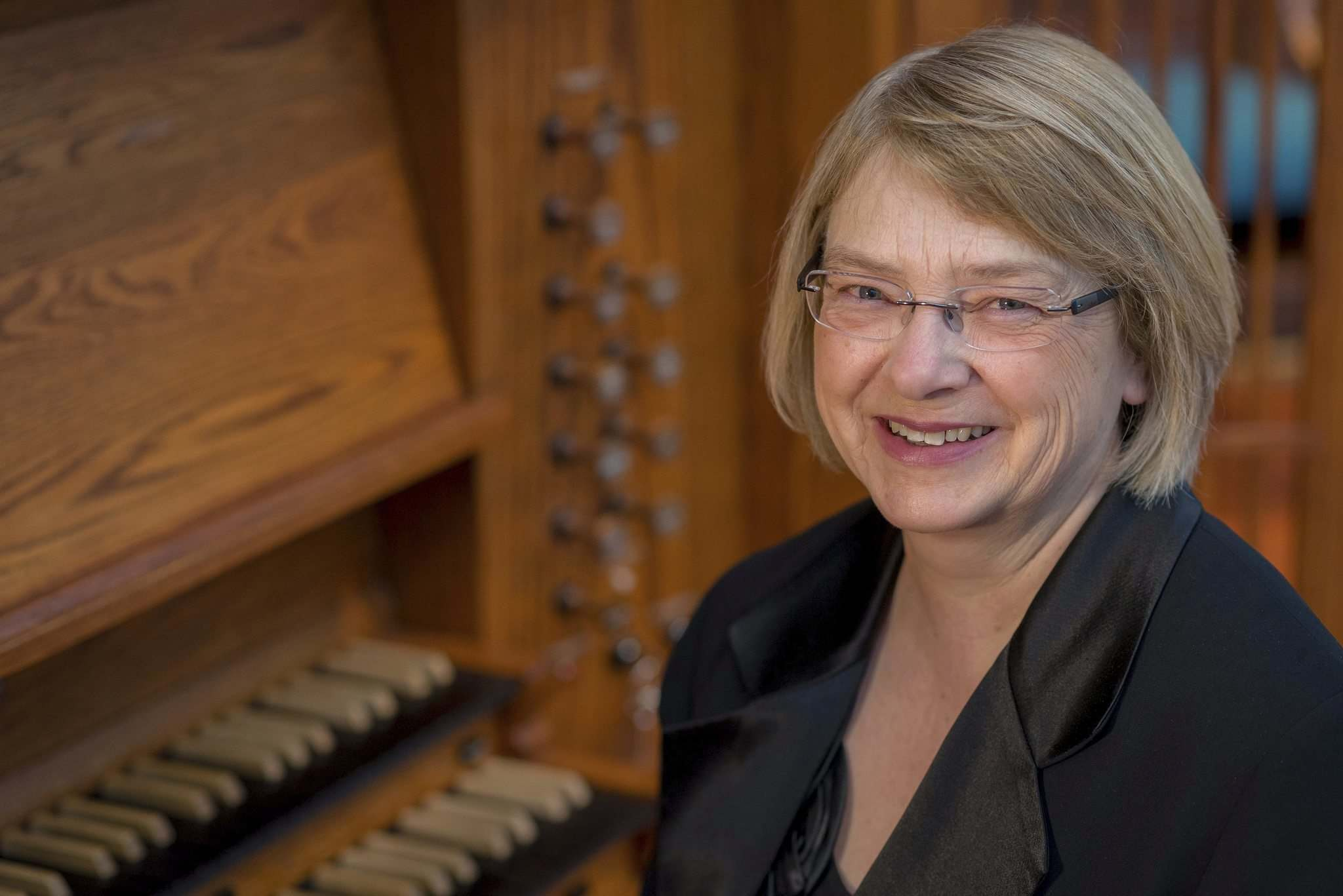Lottie Enns-Braun, organist at Young United Church, sits with the church's organ. (Anthony Mark Schellenberg photo)</p>