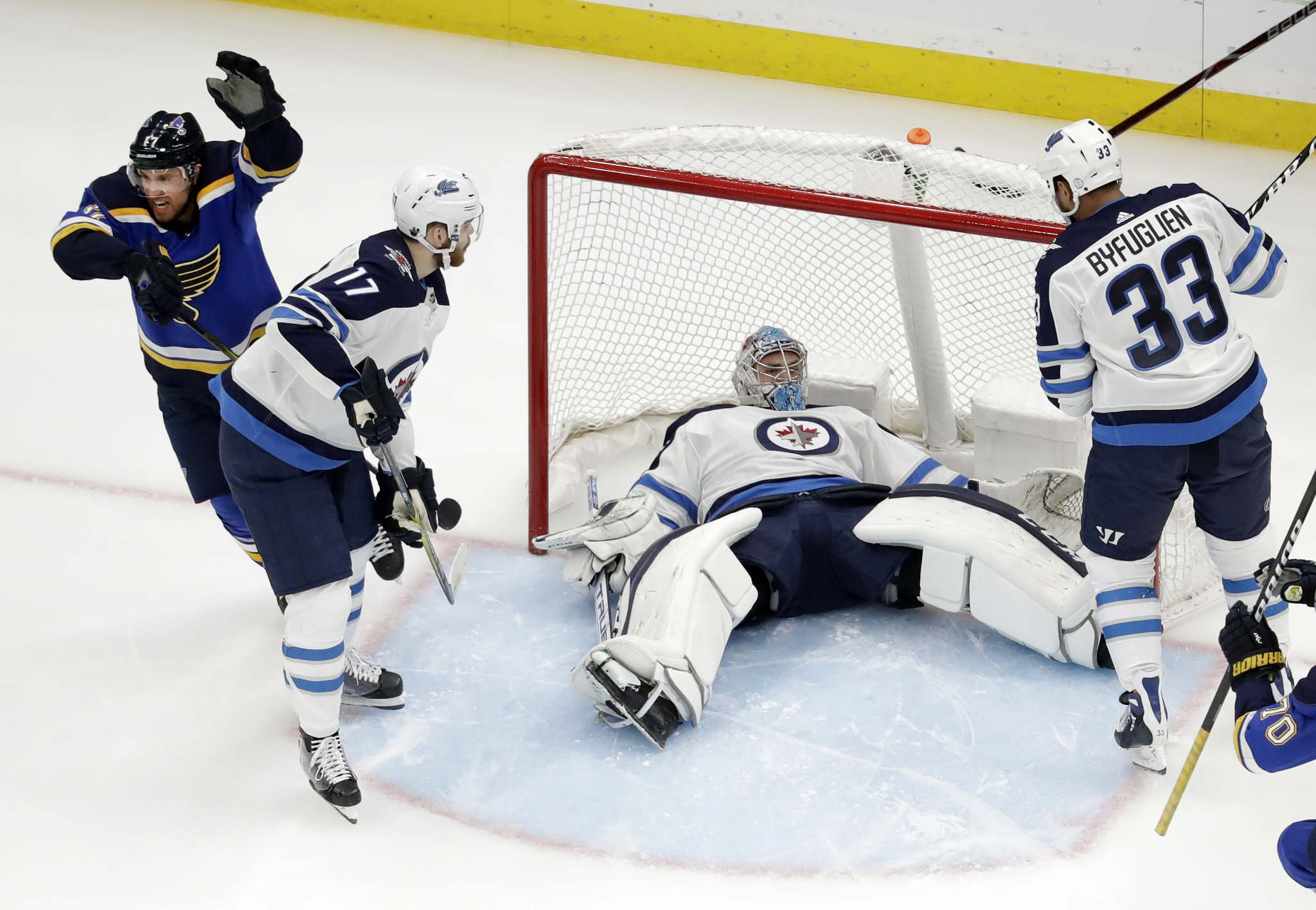 St. Louis Blues' Jaden Schwartz, left, celebrates after scoring past Winnipeg Jets goaltender Connor Hellebuyck who lies in the net as Jets' Adam Lowry, second from left, and Dustin Byfuglien (33) watch during the first period in Game 6 of an NHL first-round hockey playoff series, Saturday, April 20, 2019, in St. Louis. (AP Photo/Jeff Roberson)</p>