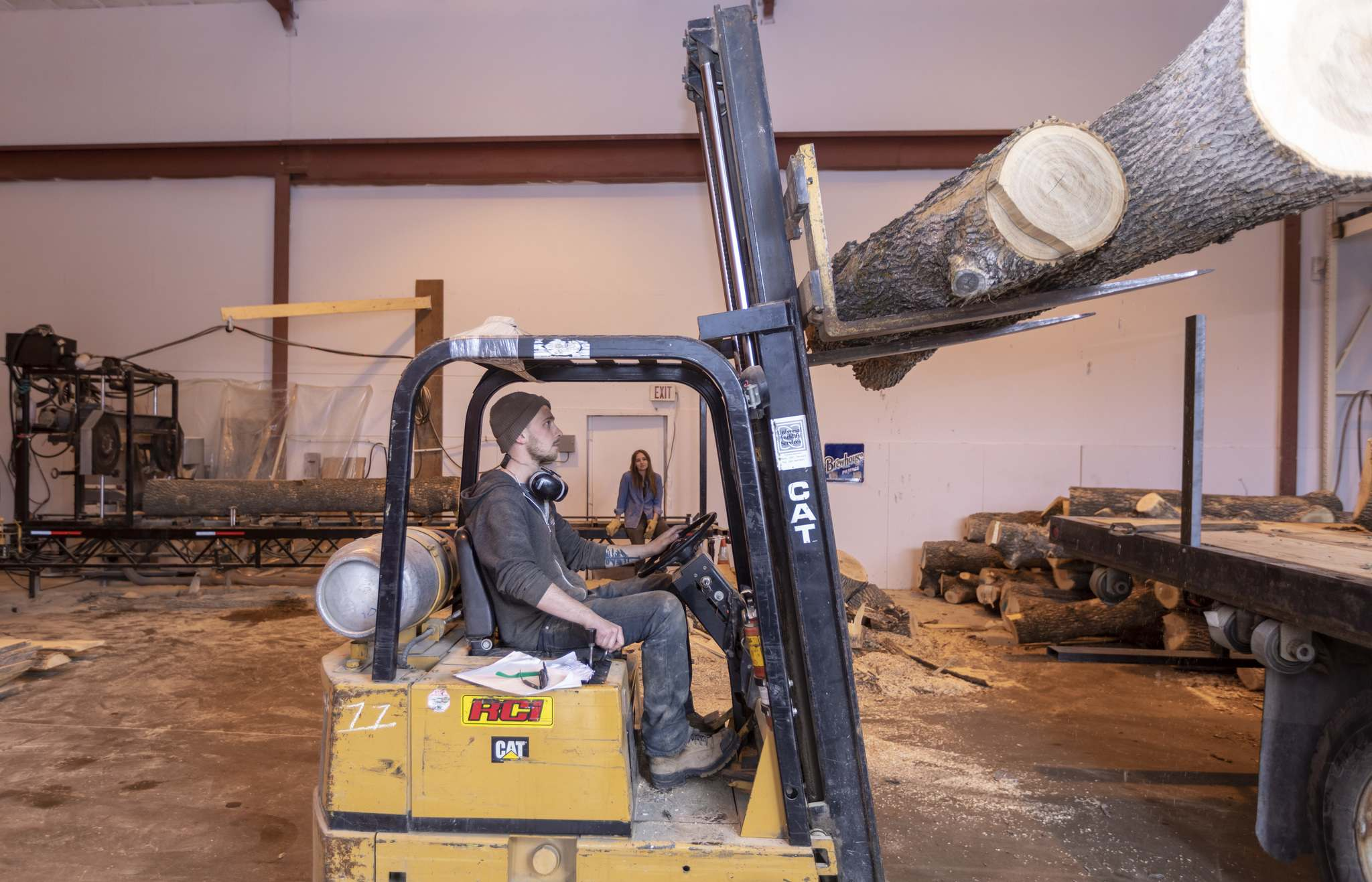 <p>McGarry uses a forklift he found in the building he rented to unload trees to be processed.