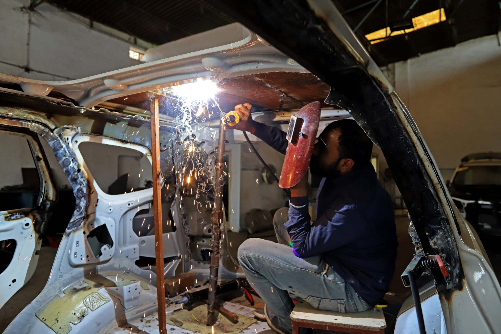 Anindito Mukherjee / Bloomberg</p><p>A worker welds armour to the roof of an SUV at a factory in Jalandhar, India. </p>