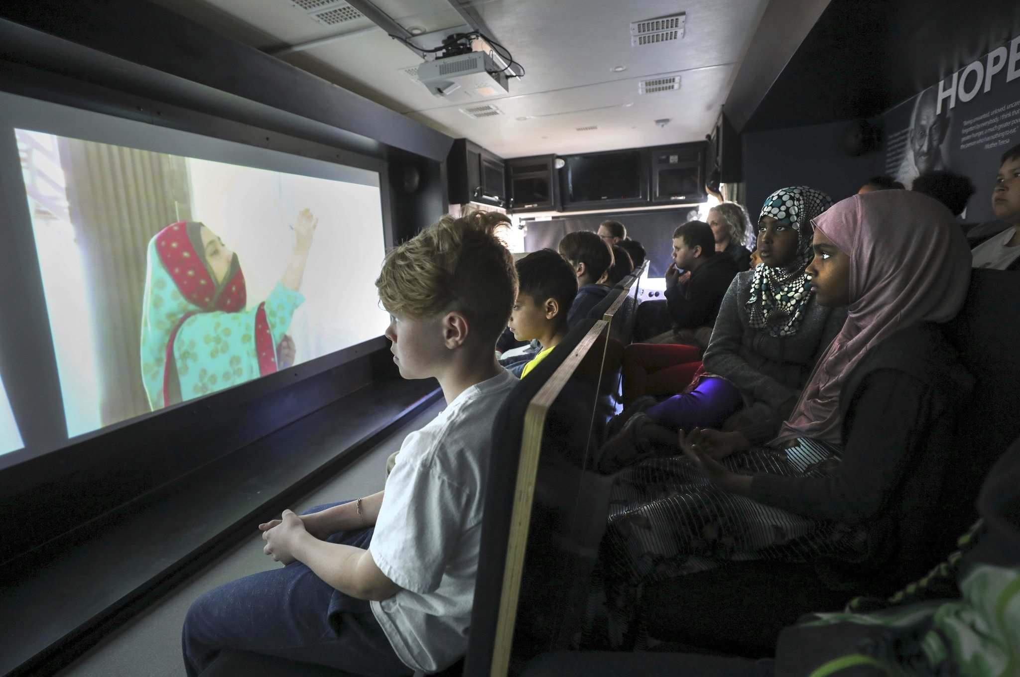 RUTH BONNEVILLE / WINNIPEG FREE PRESS </p><p>Students from Mulvey School watch a video on Hope while seated on the Simon Wiesenthal Center's Humanity Bus while it's stopped at their school for classroom teaching sessions on Thursday. </p>