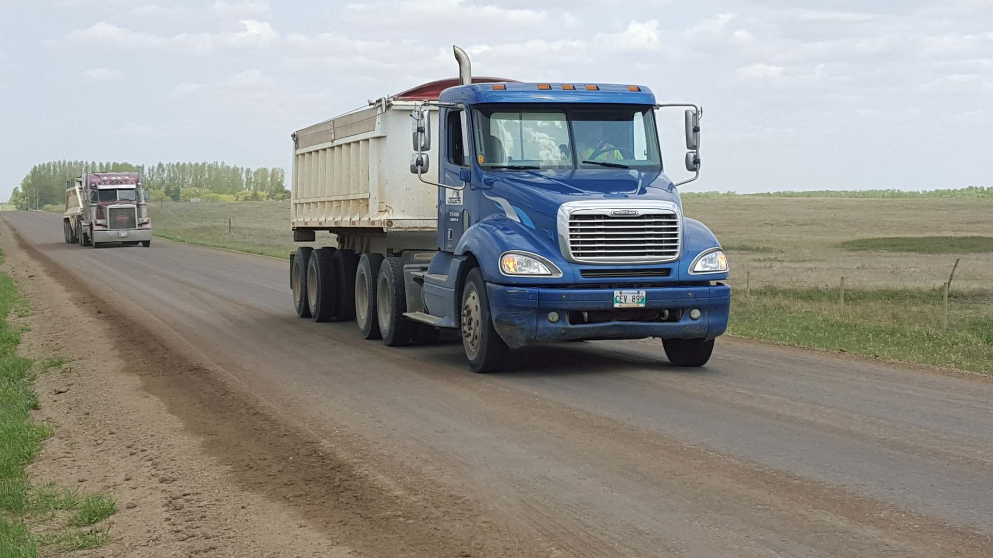 SUPPLIED</p><p>Gravel trucks spread EarthZyme on a road in the RM of Cornwallis. The cost of application is about $75,000 a kilometre. While that seems high, it makes economic sense in Cornwallis because grading and watering is more expensive.</p>