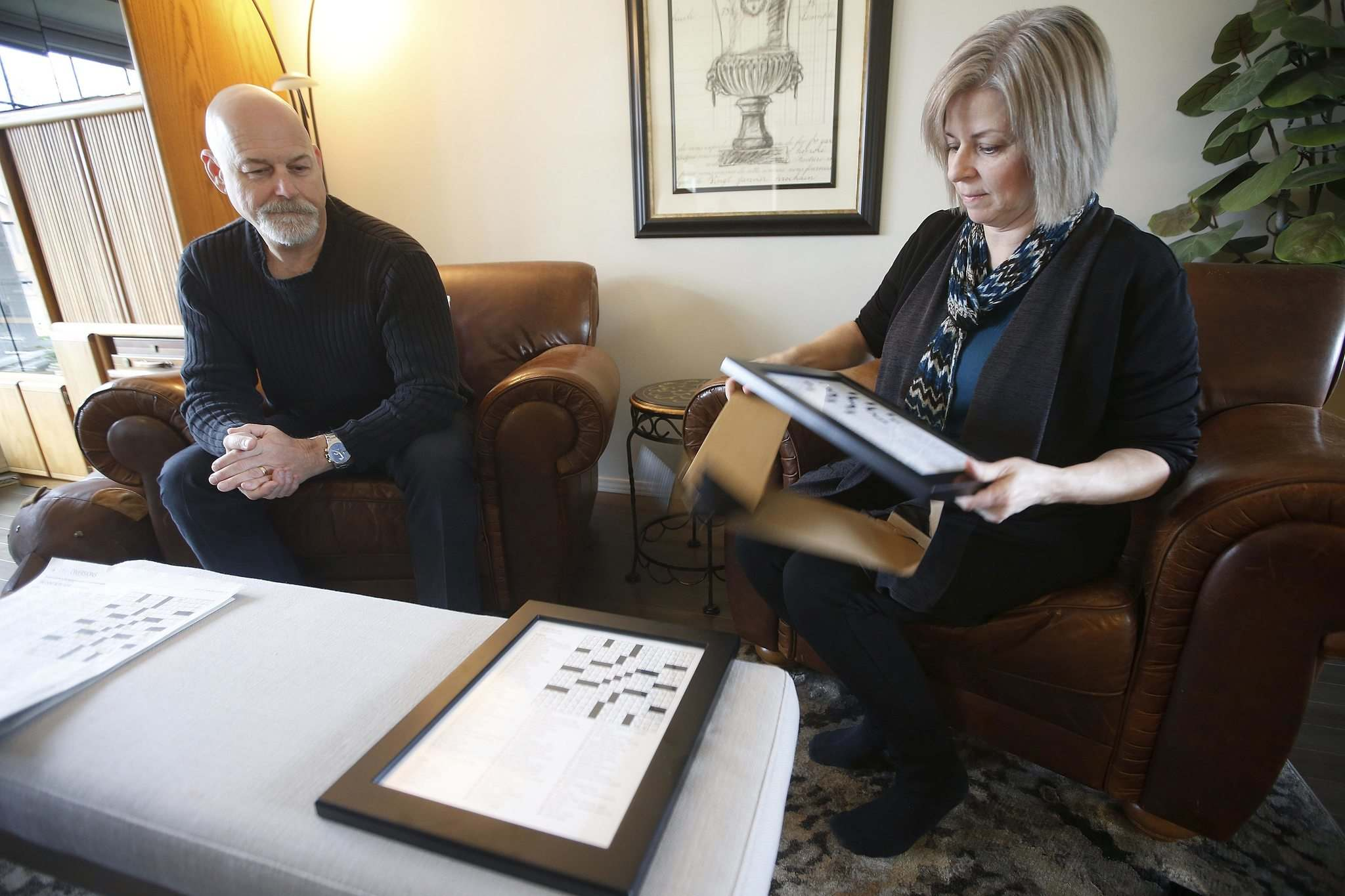 Leanne Cadieux unwraps framed copies of a personalized crossword in their home on Sunday.</p>