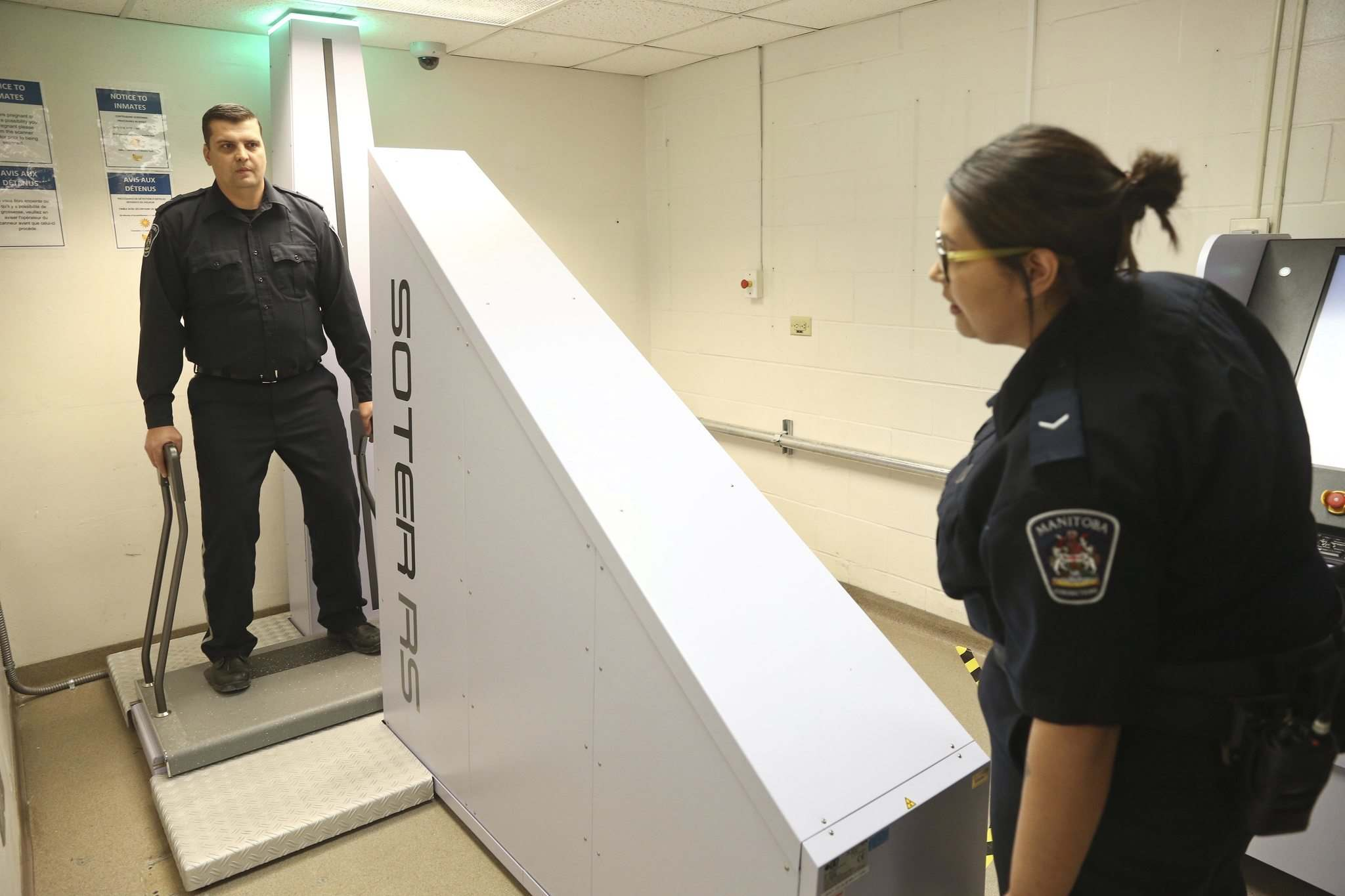Correctional Officers Melissa and Clayton test the new body scanner at the Remand Centre. (Mike Deal / Winnipeg Free Press)</p>