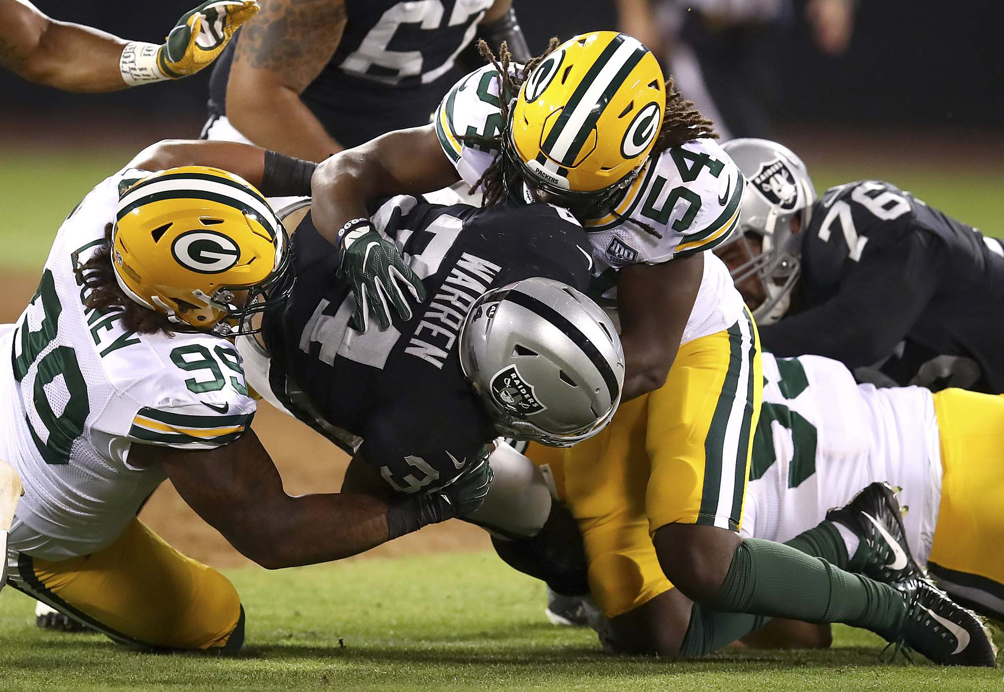 Oakland Raiders running back Chris Warren III, center, is tackled by Green Bay Packers defensive end James Looney (99) and linebacker James Crawford (54) during the second half of an NFL preseason football game in Oakland, Calif., Friday, Aug. 24, 2018. (AP Photo/Ben Margot)</p>
