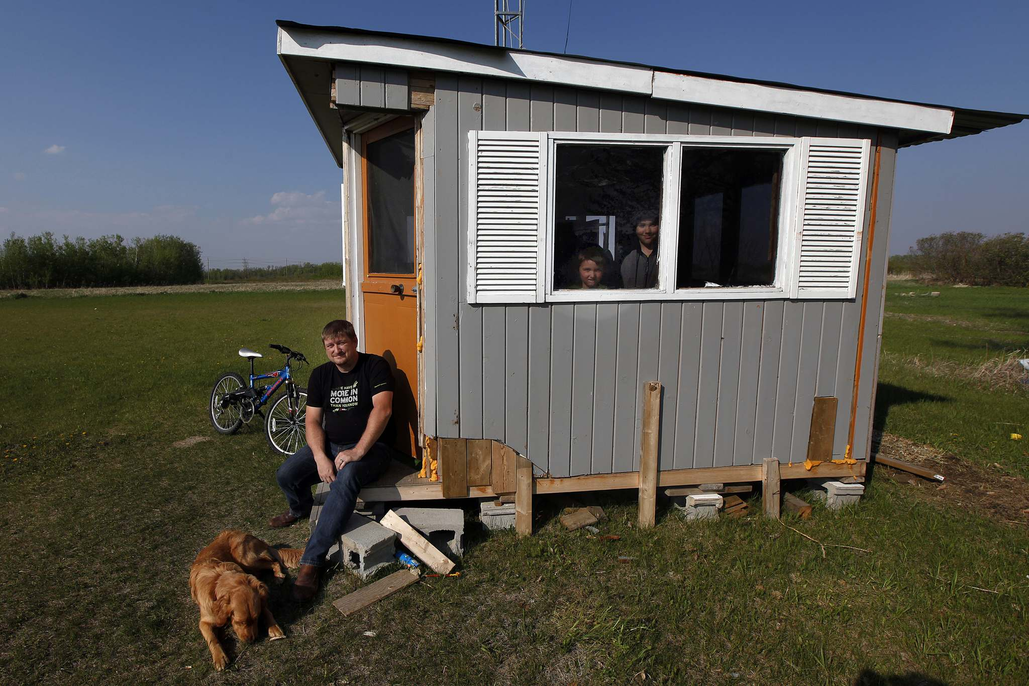 Fleury sits on the step of his Ham Shack in East Kildonan while his sons Billy, 7, and Avi, 12, peer out the window. (Phil Hossack / Winnipeg Free Press)