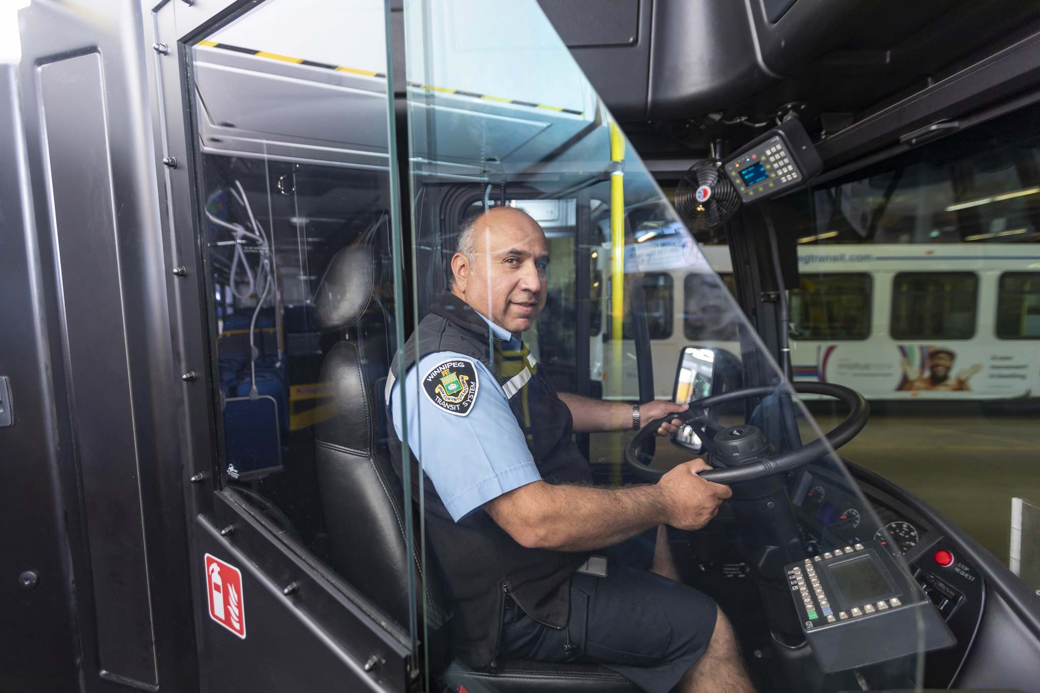 Transit driver Angel Valazquez sits in a bus with a new safety shield during a press conference Thursday. Two contractors submitted acceptable designs and the winner was selected by drivers during a nine-month test period. (Sasha Sefter / Winnipeg Free Press)</p>