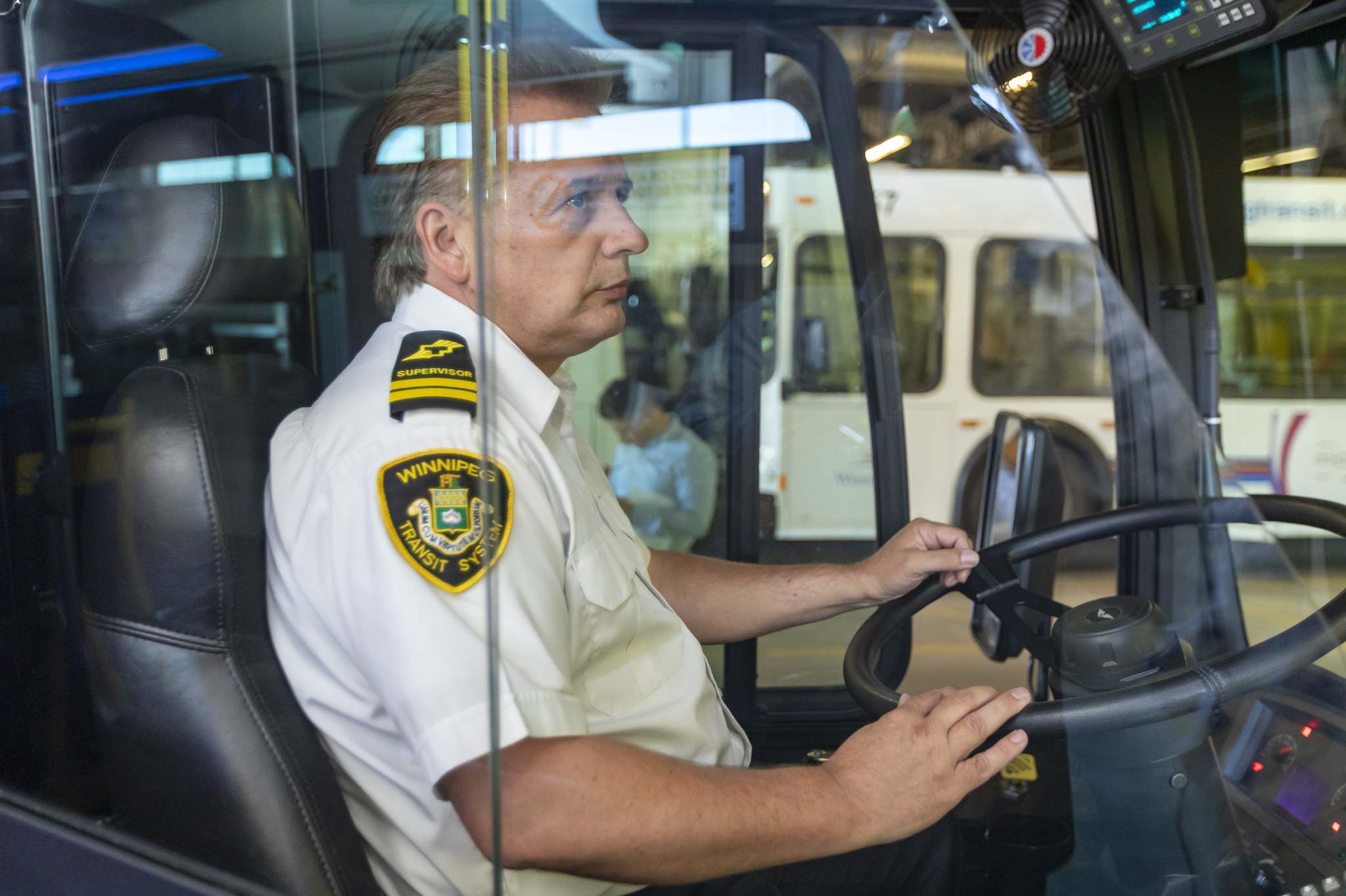 Blaine Early, Winnipeg Transit's chief timekeeper, checks out the new safety shield, which will be installed at a rate of 15 per week for 42 weeks. (Sasha Sefter / Winnipeg Free Press)</p>