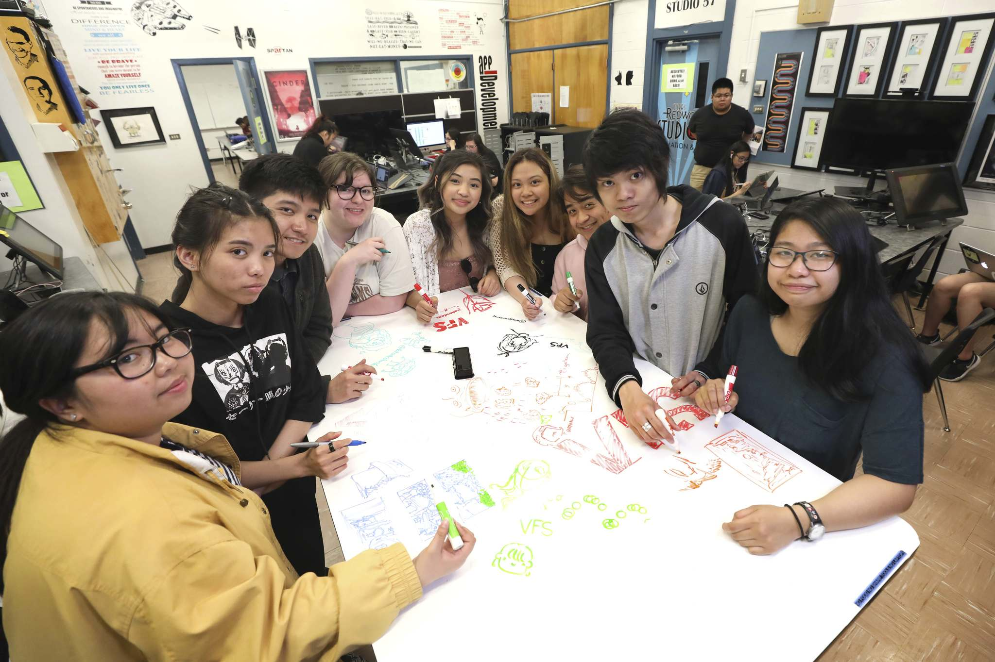 Sisler students brainstorm ideas on a whiteboard table in the school's Redwood Animation Studio.</p>