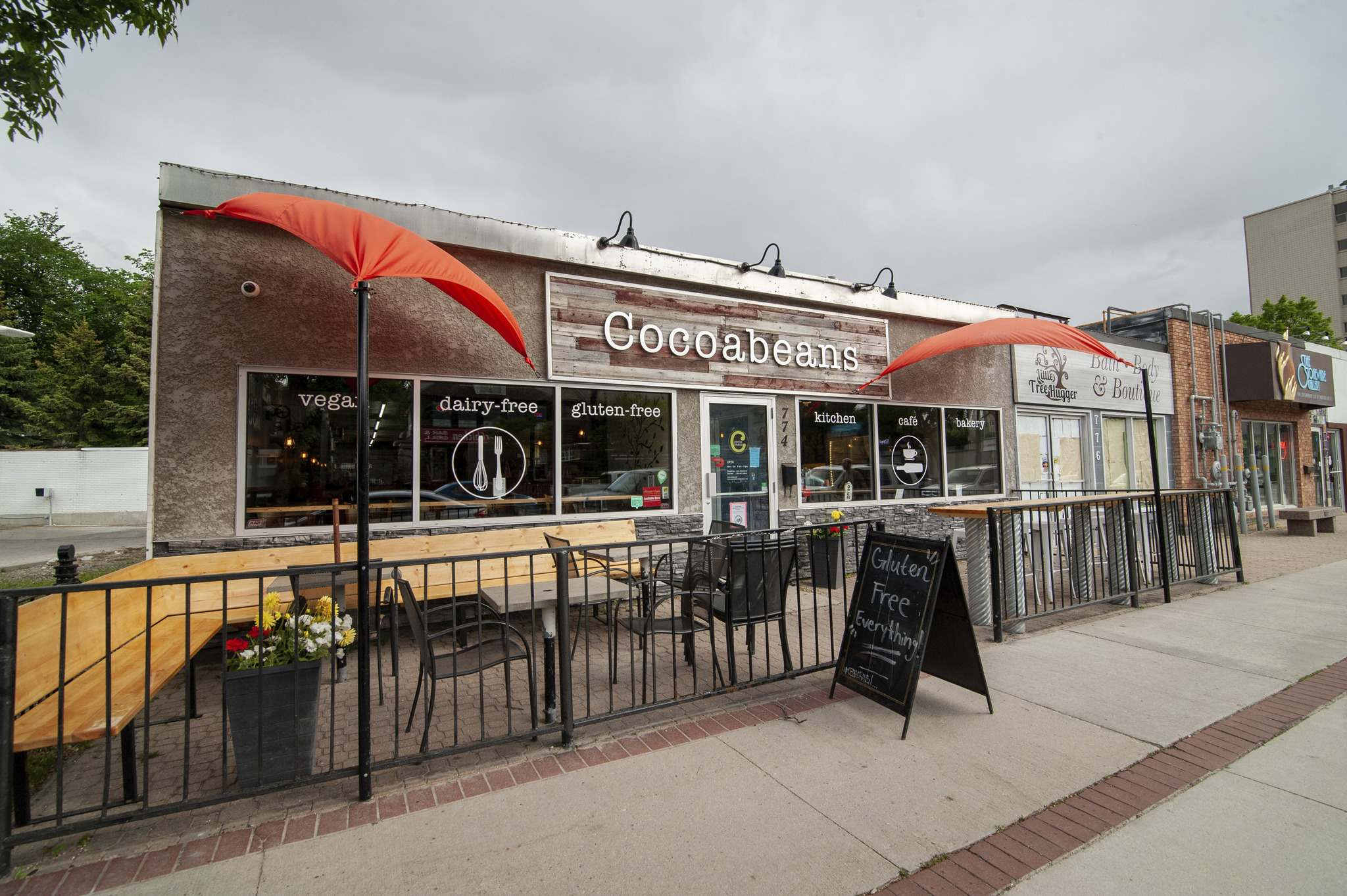 The patio on the southside of Cocoabeans Bakeshop and Cafe on Corydon Avenue features a wood bench and a tall tabletop with stools. (Mike Sudoma / Winnipeg Free Press)