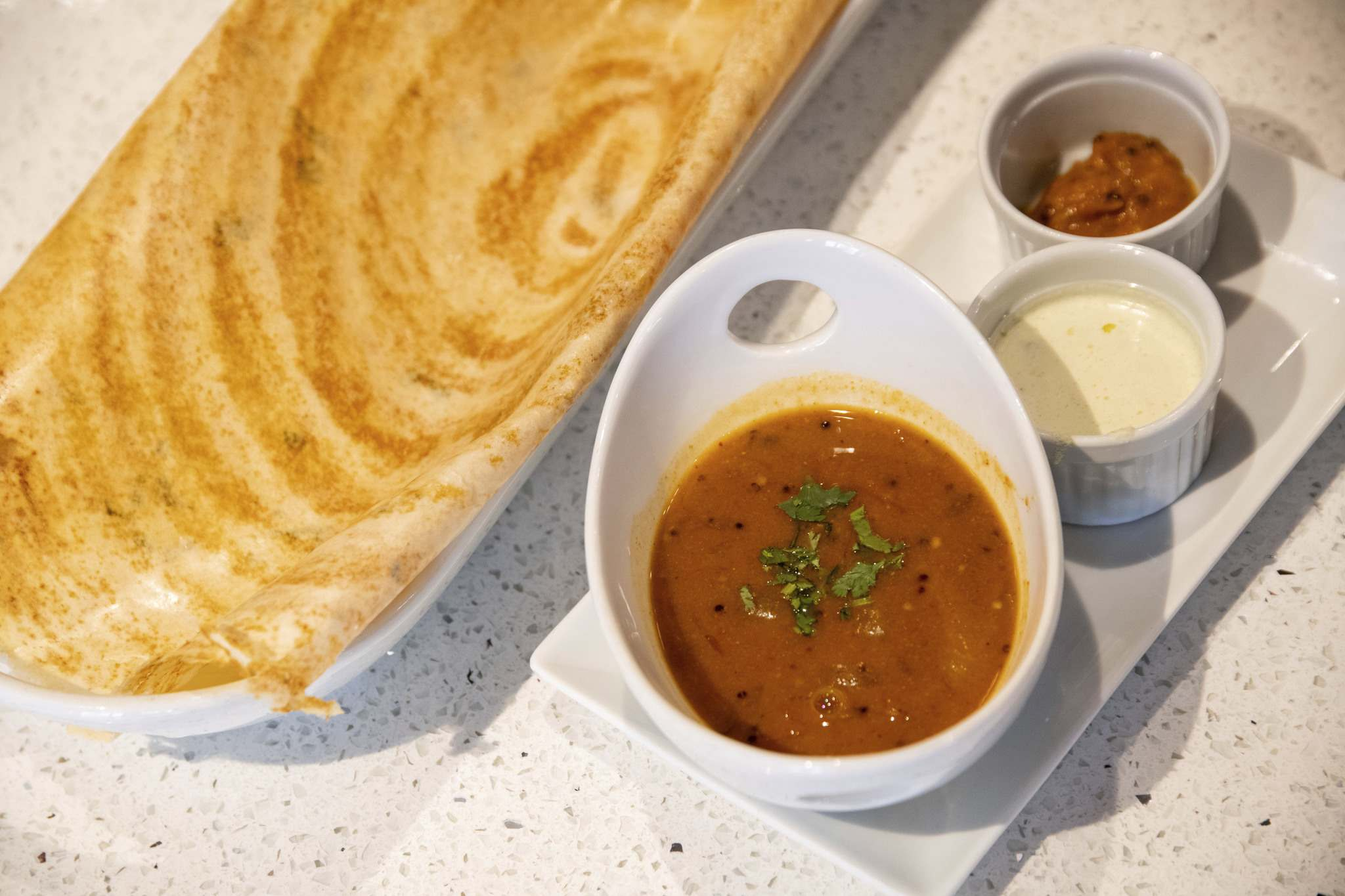A plate of Masala Dosa, served with lentil soup and an assortment of dips.</p>