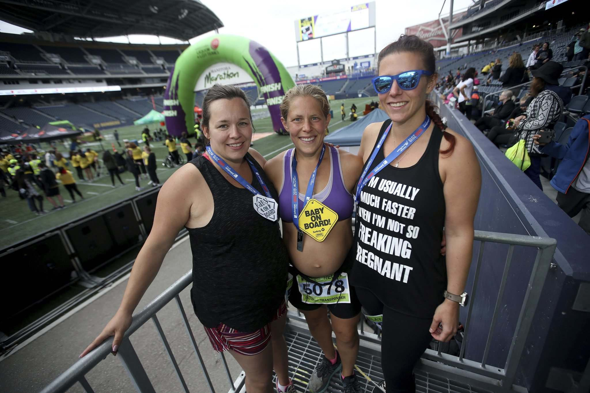 Ashly Reyes, Reesa Simmonds and Breanne Peters, part of an all-pregnant relay team, gather at the finish line Sunday. (Trevor Hagan / Winnipeg Free Press)
