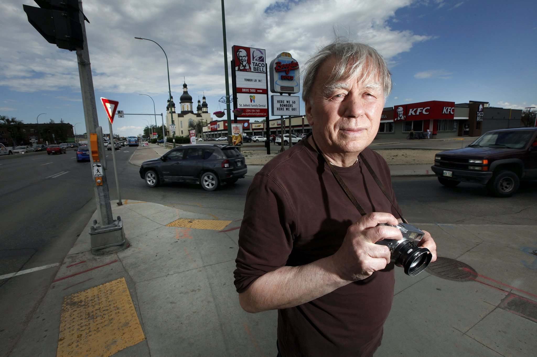 PHIL HOSSACK / WINNIPEG FREE PRESS</p><p>Photographer John Paskievich at the same intersection as his photograph 'Redwood and Main.'</p></p>