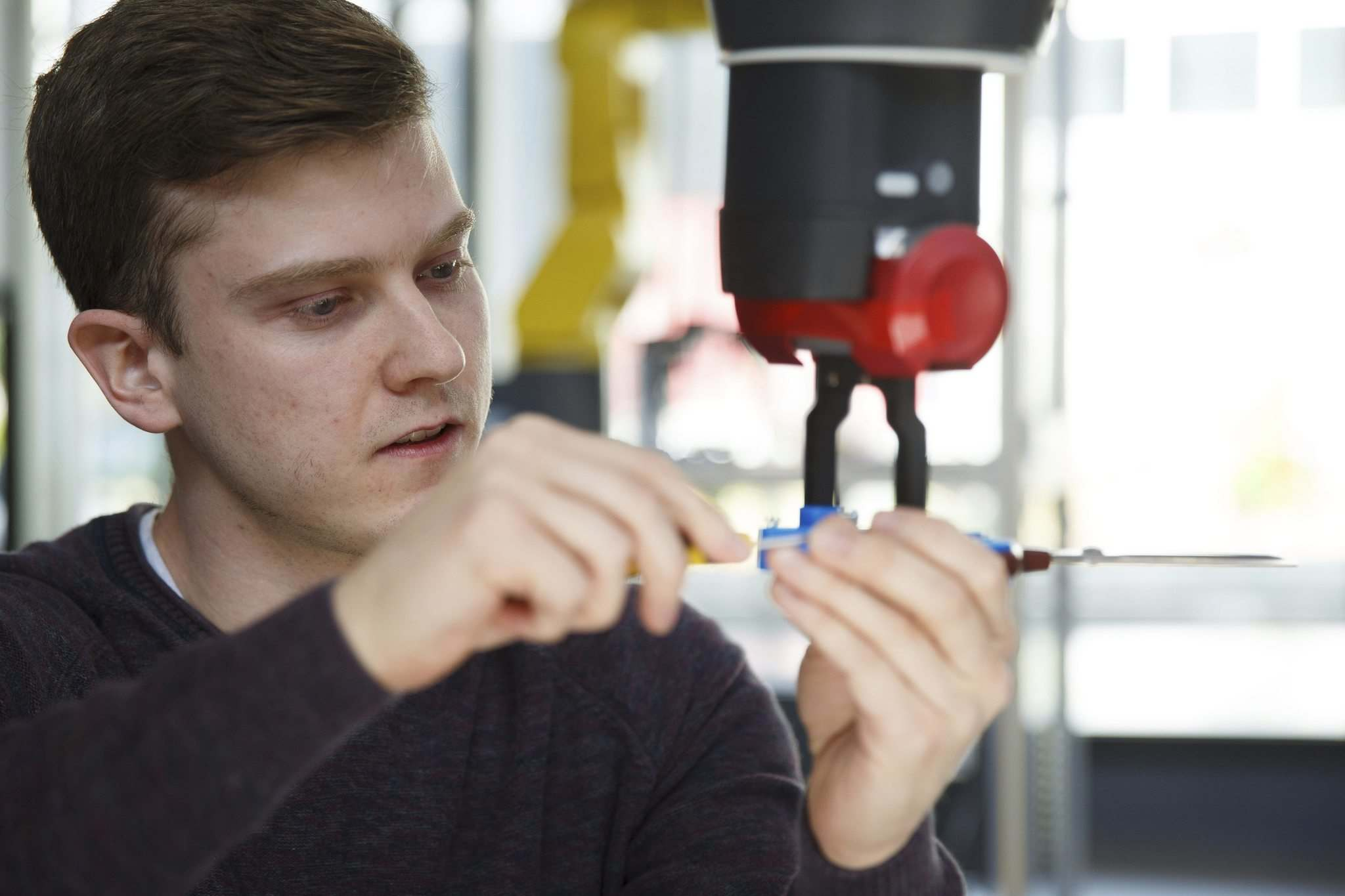 <p>Riley Cornelius, a second year electronic engineering co-op student, adjusts the scissors for robot Baxter, so that it could cut the red ribbon to officially open the new Smart Factory.</p></p>