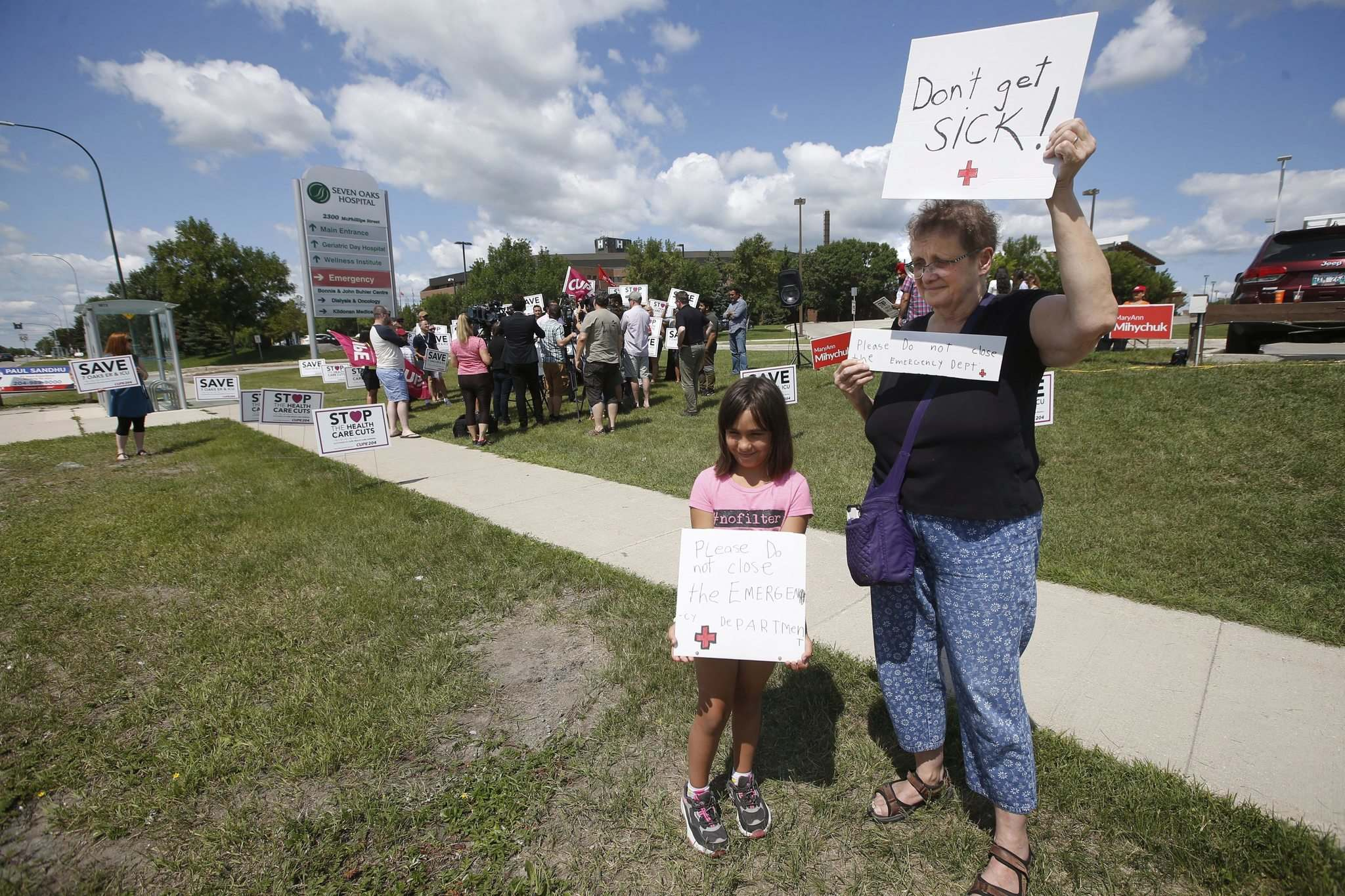 JOHN WOODS / WINNIPEG FREE PRESS</p><p>Pam Semchych and her granddaughter Elize, 7, hold signs as Wab Kinew talks to media to oppose the transition of Seven Oaks Emergency to an Urgent Care Centre.</p>