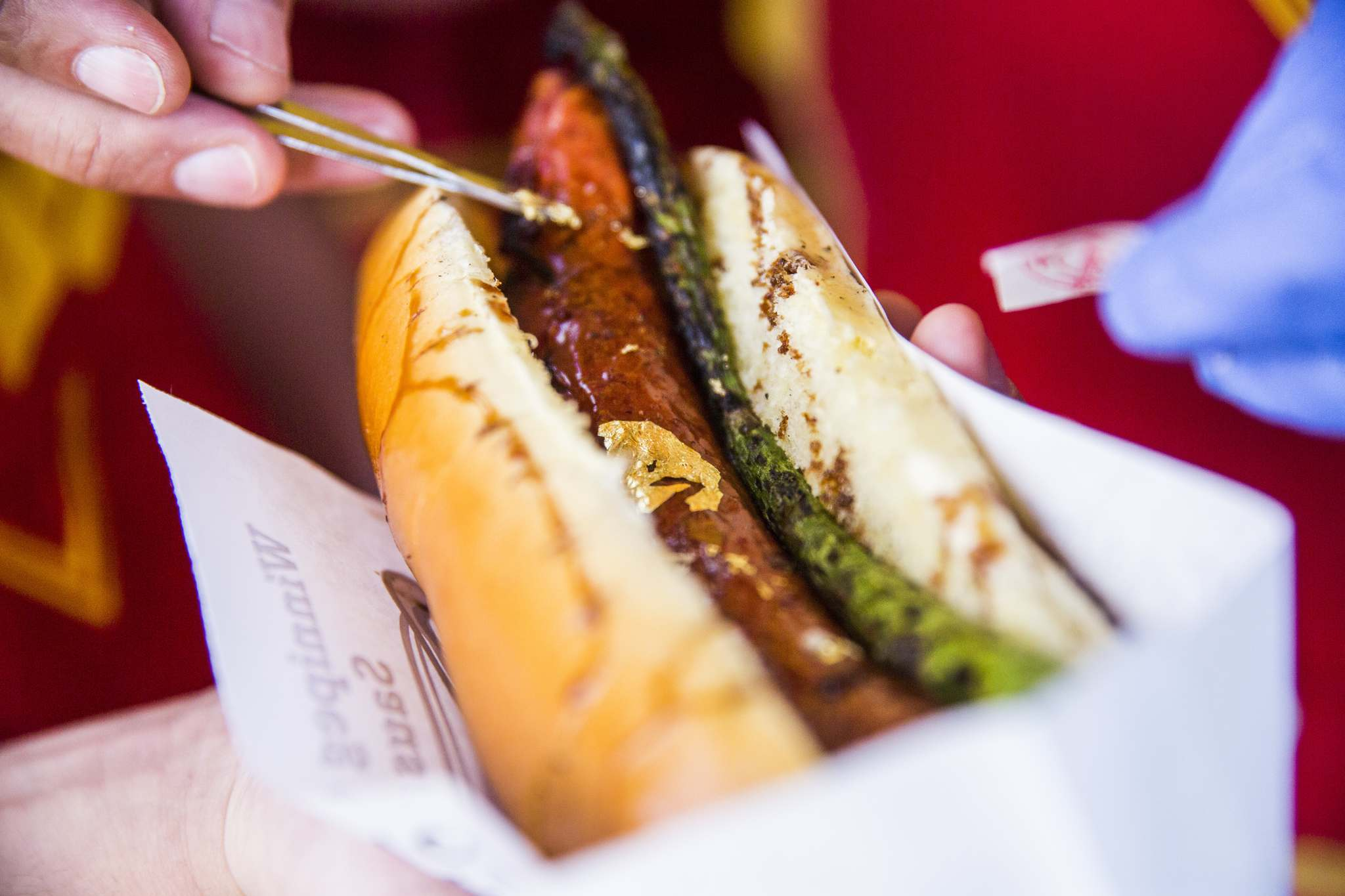 MIKAELA MACKENZIE / WINNIPEG FREE PRESS</p><p>The $100 golden smokie is topped with truffle oil, a balsamic reduction and real gold leaf. A single spear of garlic-flavoured asparagus is also inside the Gunn's Bakery bun.</p>