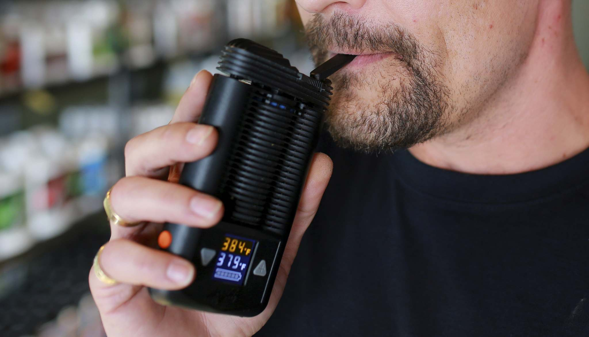 A man uses a hand-held dry-herb vaporizer, which heats cannabis without burning it.</p>