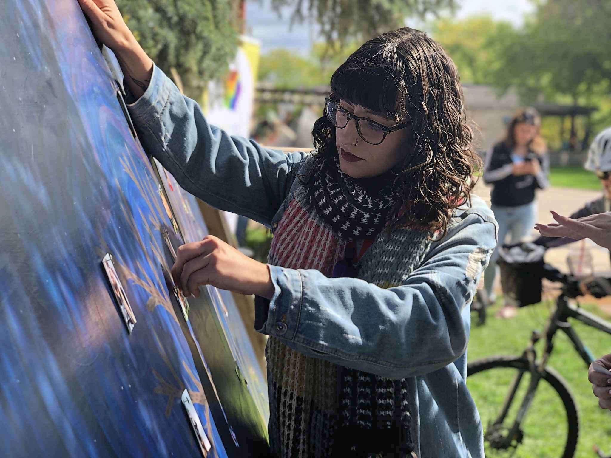 Artist Ruby Rain pins a photo of a loved one lost to overdose on her painting of a tree at Recovery Day. (Tessa Vanderhart / Winnipeg Free Press)</p>