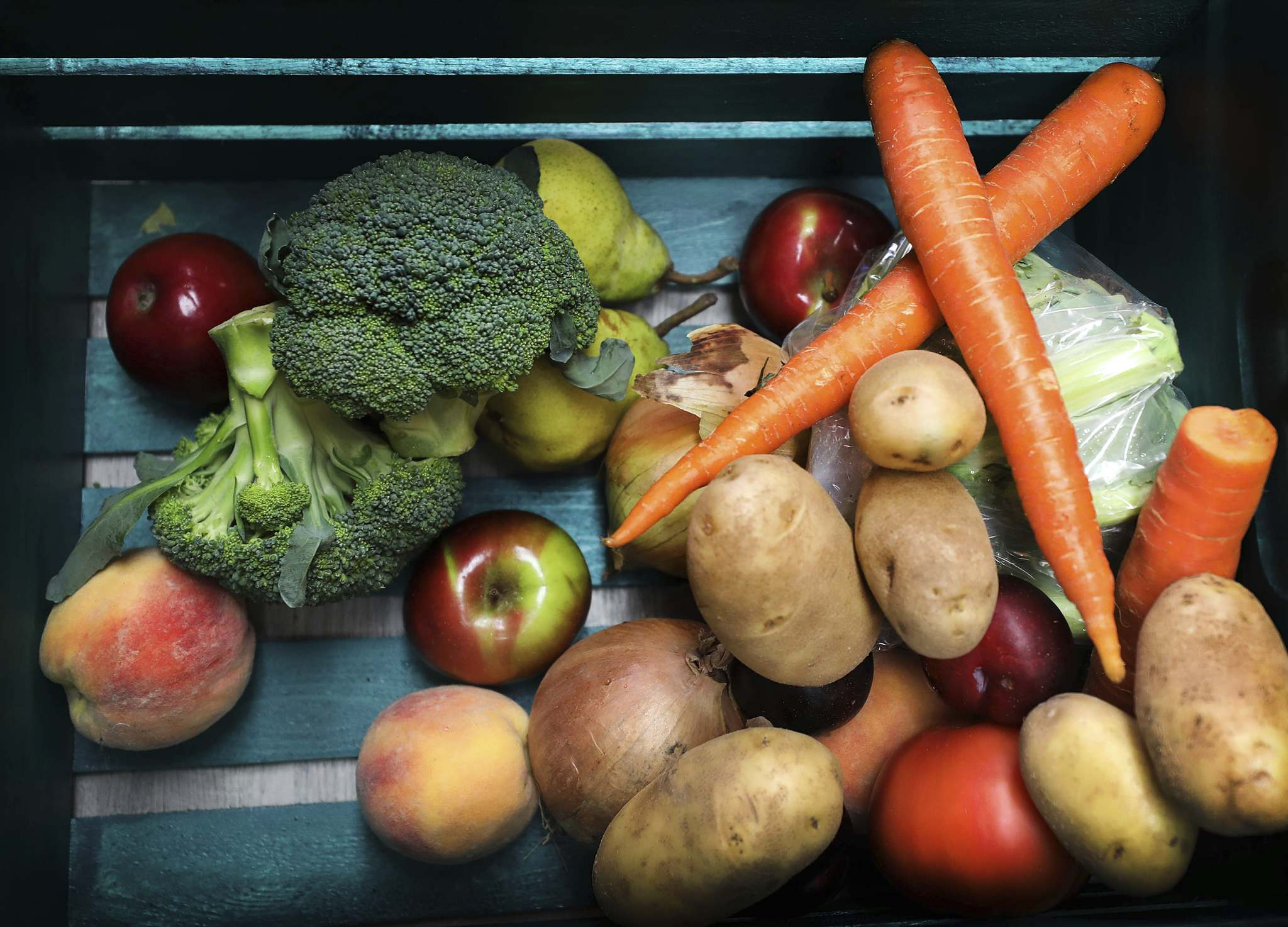 A crate half loaded with fresh fruits and veggies. More items will still go into the crate.
