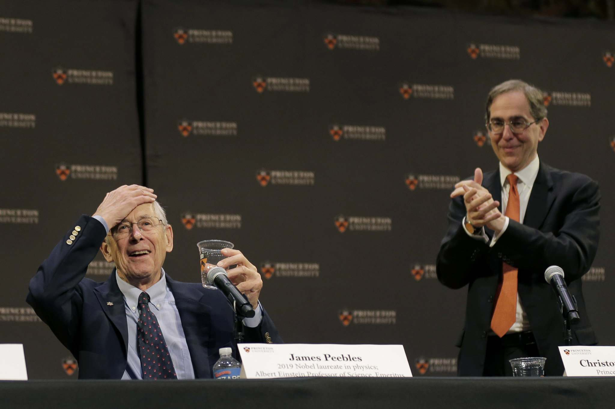 James Peebles, left, reacts as people applaud, including Princeton University president Christopher Eisgruber, at a news conference at Princeton University in Princeton, N.J.Tuesday morning. (Seth Wenig / The Associated Press(