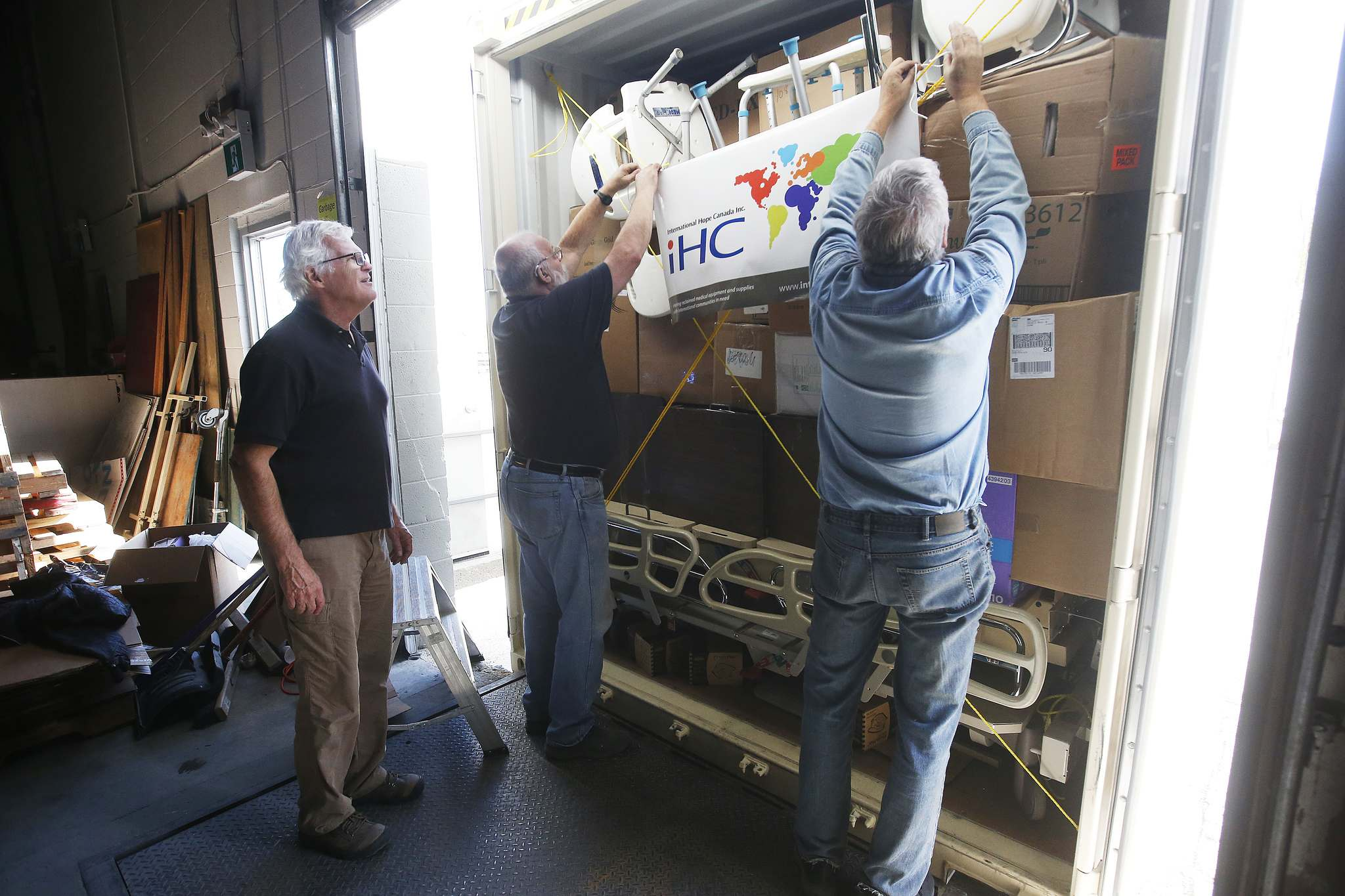 <p>Kevin Stewart, left, and other volunteers put the finishing touch on a load of reclaimed medical equipment and supplies destined for Guatemala in their Winnipeg warehouse Tuesday.</p>