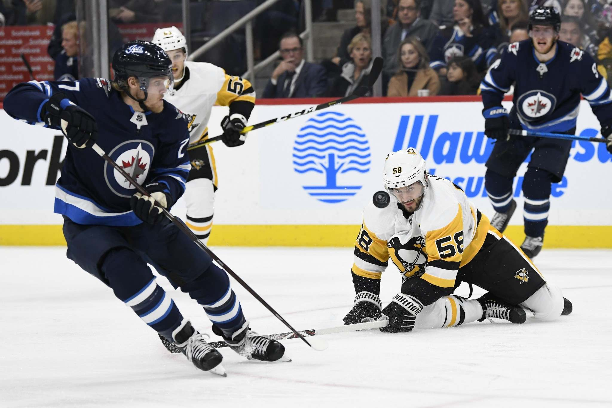 Pittsburgh Penguins' Kris Letang (58) keeps his eyes on the puck as Winnipeg Jets' Nikolaj Ehlers (27) skates down ice during first second NHL action in Winnipeg on Sunday, Oct. 13, 2019. THE CANADIAN PRESS/Fred Greenslade</p>