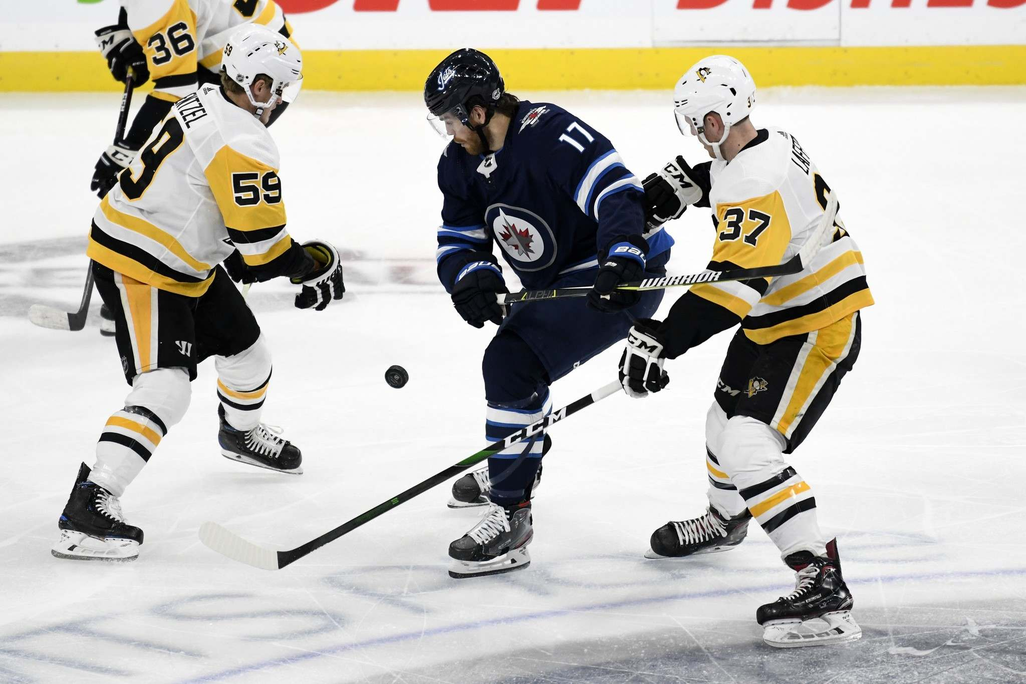 "FRED GREENSLADE / THE CANADIAN PRESS</p> <p>Winnipeg Jets' Adam Lowry (17) battles with Pittsburgh Penguins' Jake Guentzel (59) and Sam Lafferty (37) for the puck during first period NHL action in Winnipeg on Sunday, Oct. 13, 2019.</p> <p>""></a><figcaption readability="