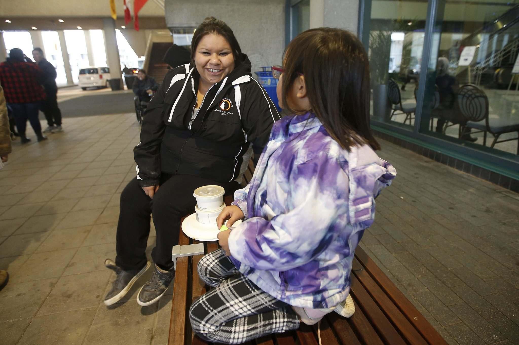 Tysha Assiniboine, from Dakota Plains First Nation, talks to her daughter Gracie outside the convention centre Tuesday. (John Woods / Winnipeg Free Press)