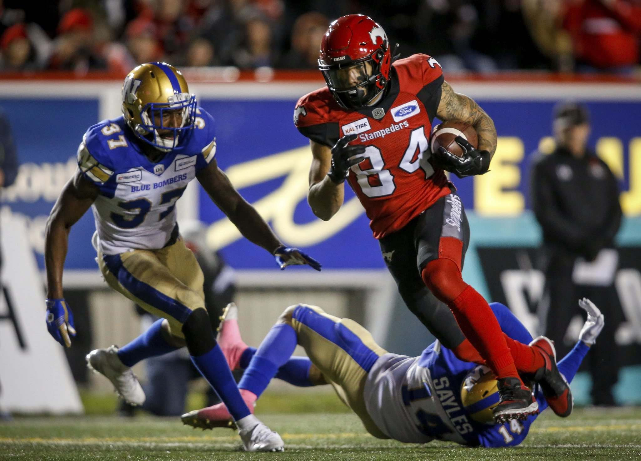 Jeff McIntosh / The Canadian Press Files</p> Bombers' Brandon Alexander (left) looks on as Stampeders' Reggie Begelton runs in his third touchdown.