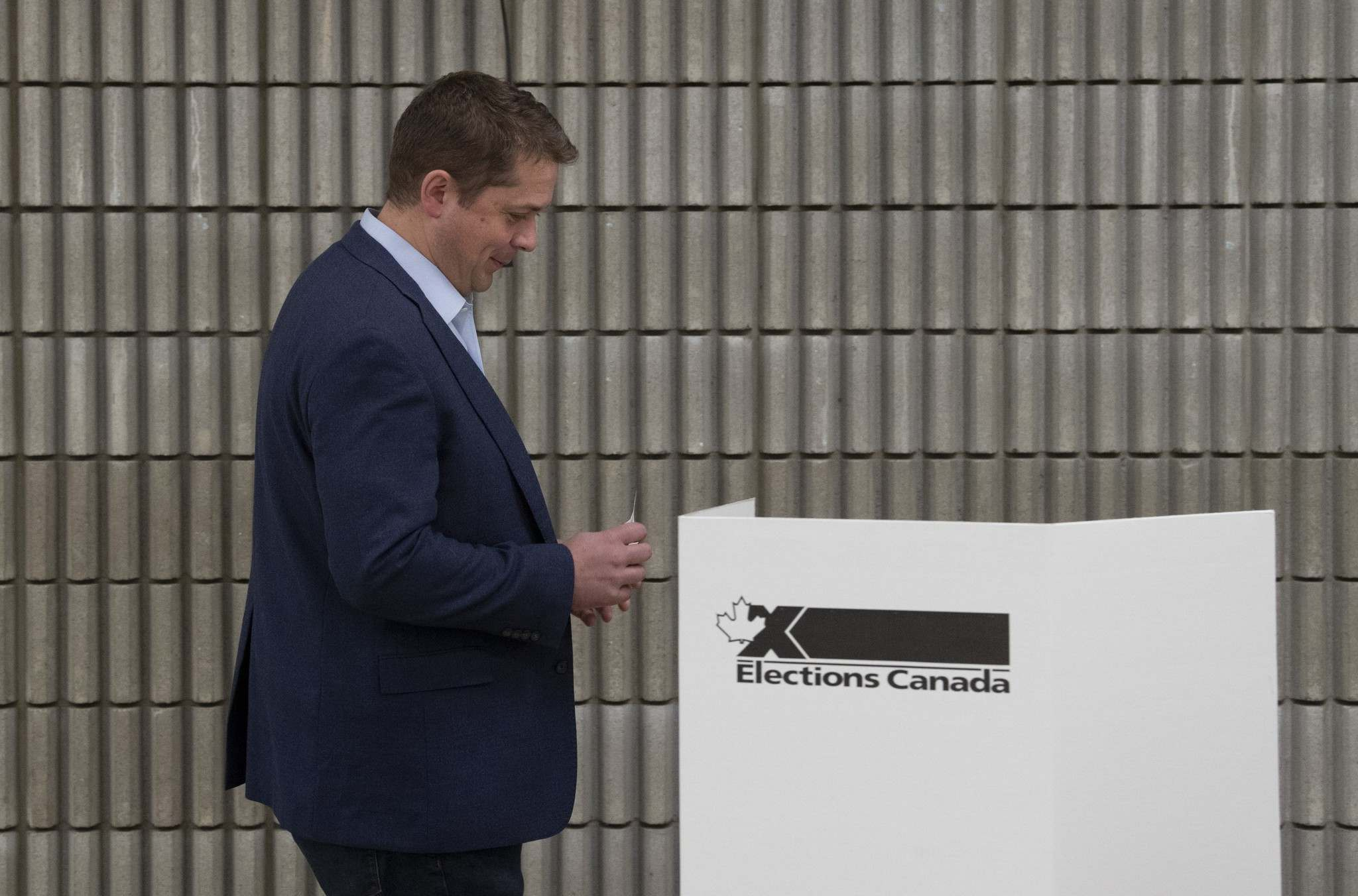 <p>Conservative leader Andrew Scheer makes his way to the voting booth to cast his ballot in Regina, Monday.