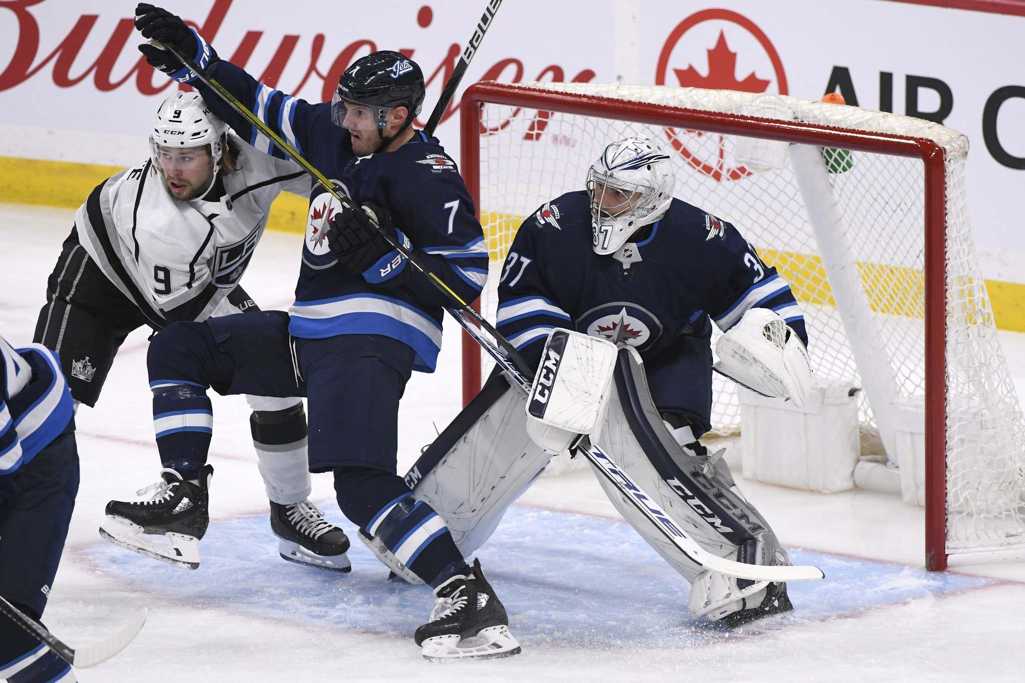 <p>Winnipeg Jets' Dmitry Kulikov and Los Angeles Kings' Adrian Kempe fight for position in front of goaltender Connor Hellebuyck in the first period.