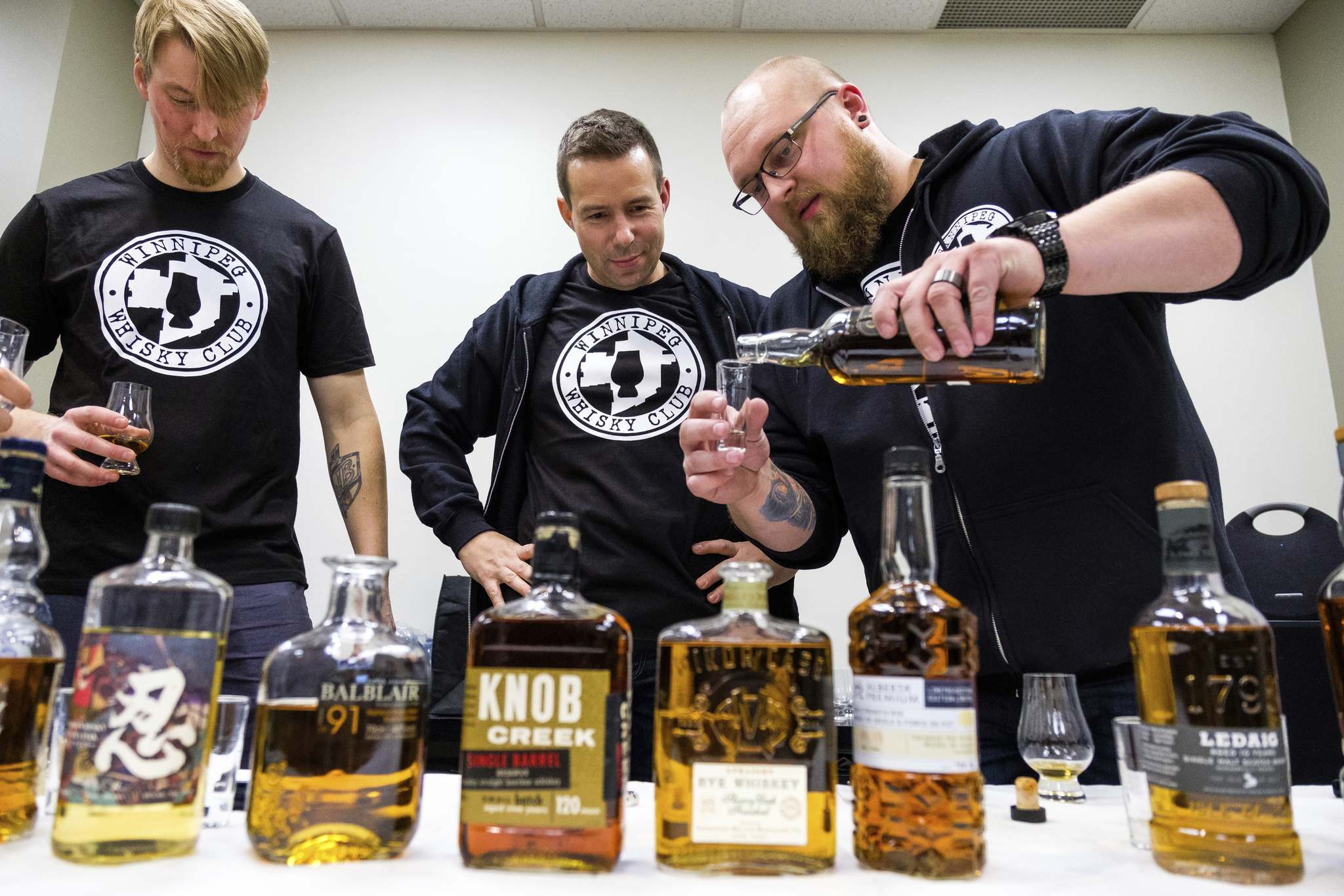 Club founder Mark Kaufmann (middle) with the evening's selection, 10 whiskies in all.</p>