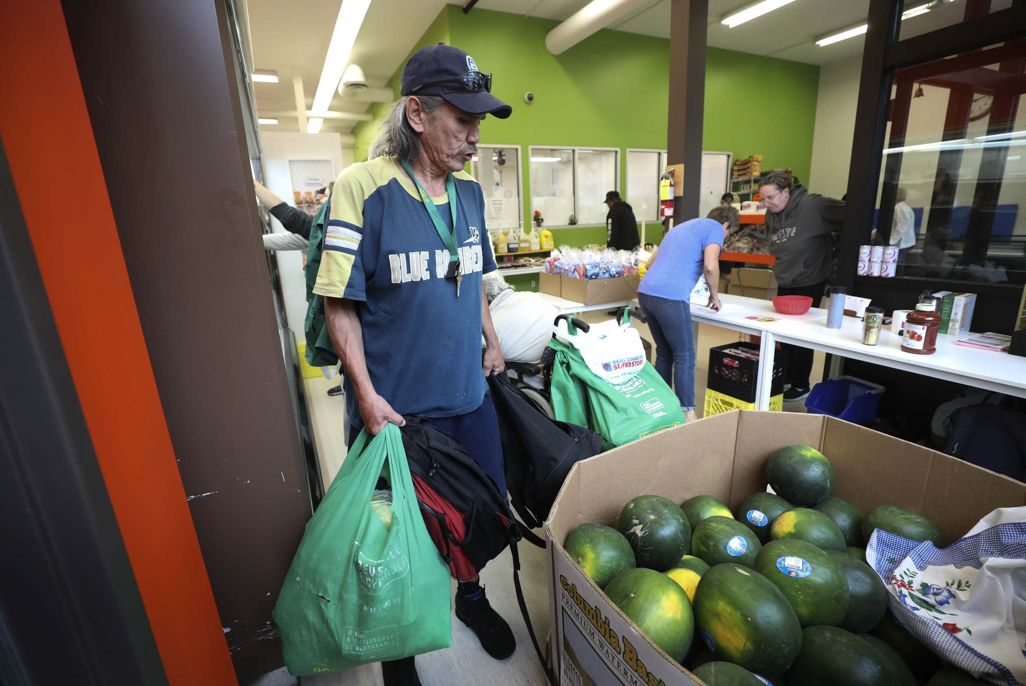 William Van Derbos carries groceries from the Main Street Project weekly food bank that includes supplies from Winnipeg Harvest. (Ruth Bonneville / Winnipeg Free Press)</p>