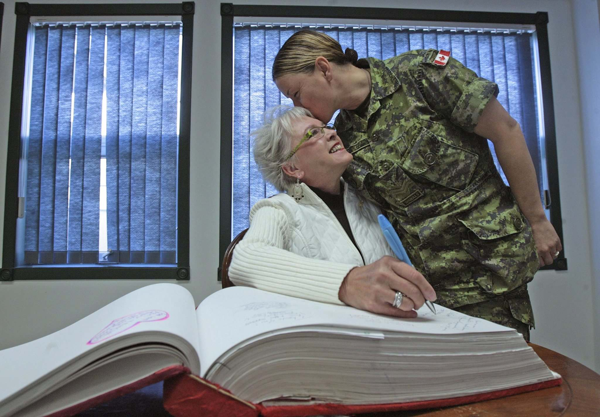 MLA Bonnie Korzeniowski gets a kiss from Master Corporal Renay Groves after she signed the National Memory Book at 17 Wing base in Winnipeg in 2007. (JOE BRYKSA/WINNIPEG FREE PRESS FILES)</p>