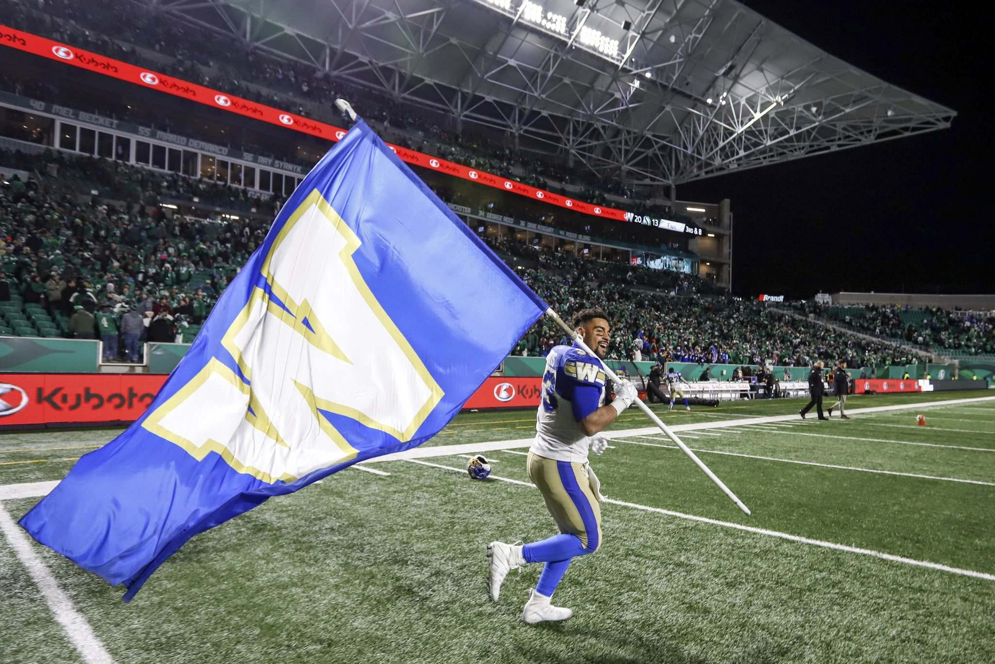 JEFF MCINTOSH / THE CANADIAN PRESS</p><p>Winnipeg Blue Bombers' Andrew Harris carries a team flag after defeating the Saskatchewan Roughriders in the CFL West Division final in Regina, Sunday.</p>