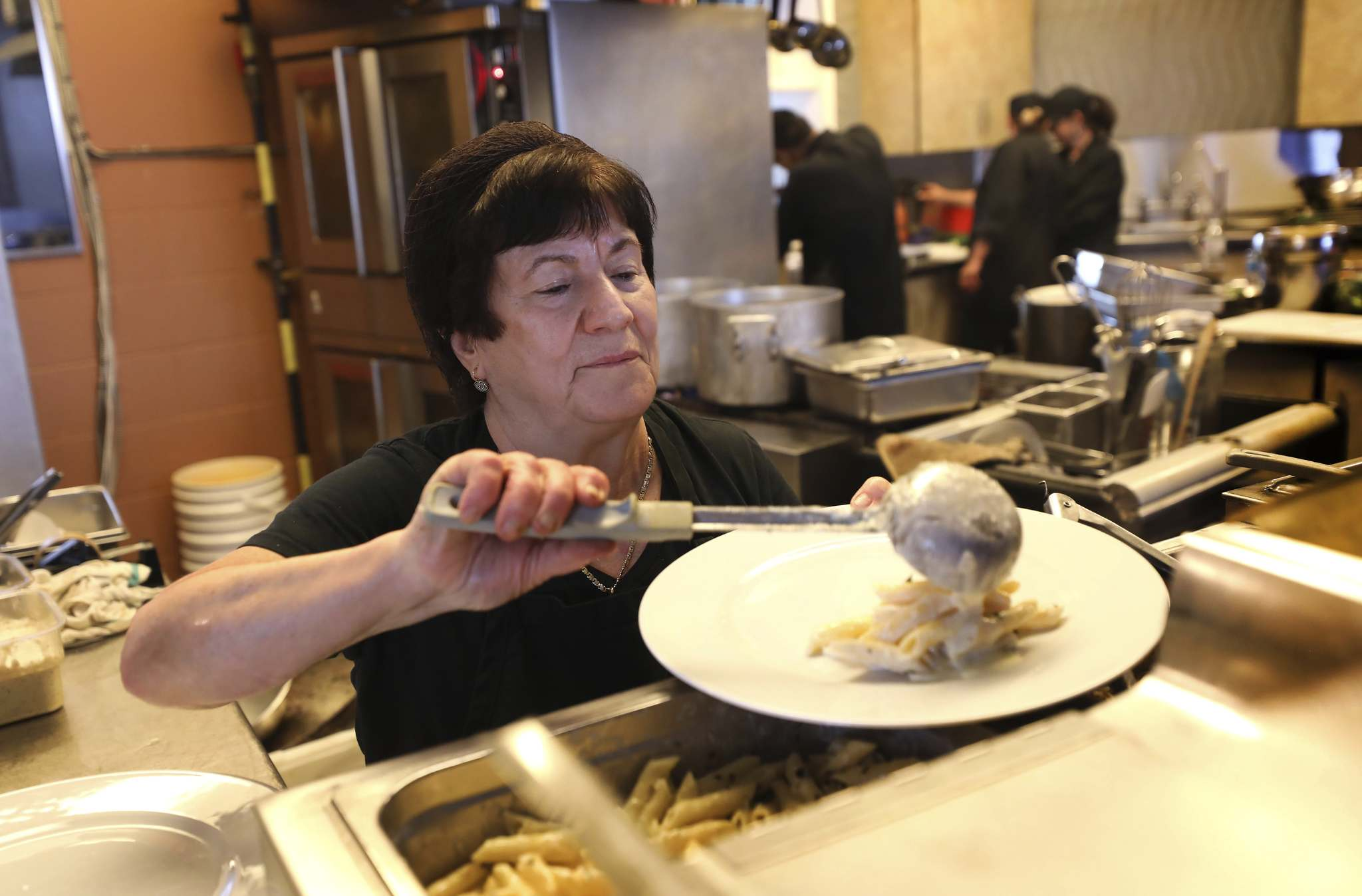 Chef Annette Santilli serves up lunch at De Luca's restaurant, known for it's all-you-can-eat buffet.