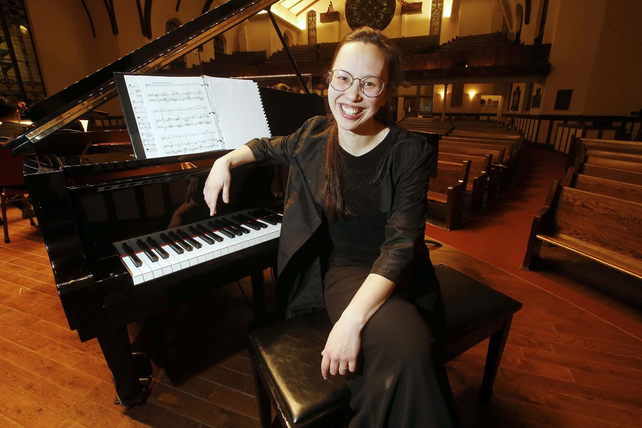 Naomi Woo, the WSO's assistant conductor, relaxes after a rehearsal at Westminster United Church. (John Woods / Winnipeg Free Press)