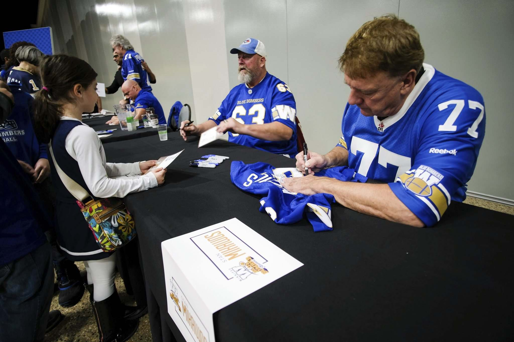 Winnipeg Blue Bomber alumni Chris Walby (left) and Stan Mikawos (right) sign autographs for fans Saturday at the convention centre. (Daniel Crump / Winnipeg Free Press)</p>