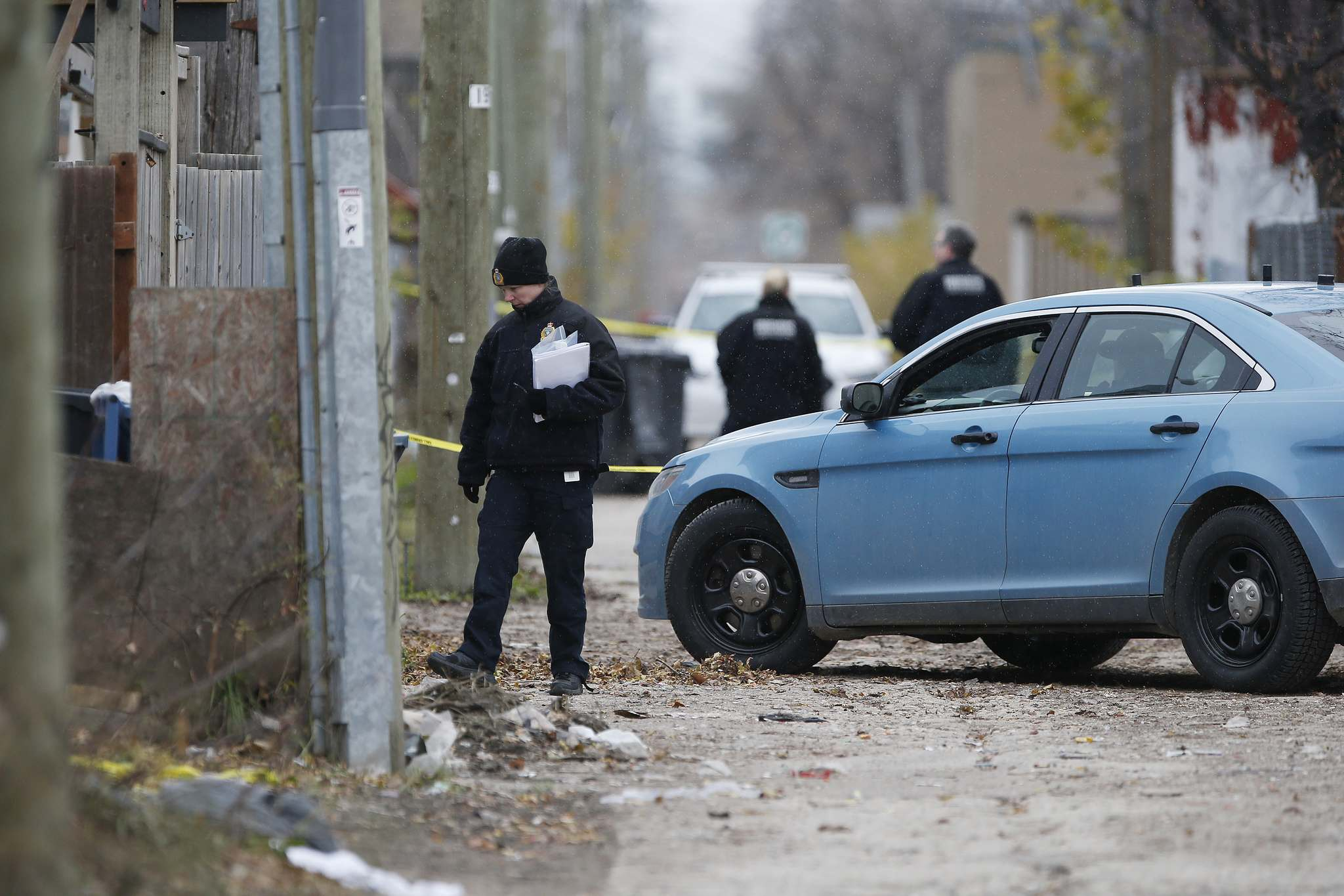 Police investigate the double homicide in the back lane between Elgin and Ross avenues in October. (John Woods / Free Press files)
