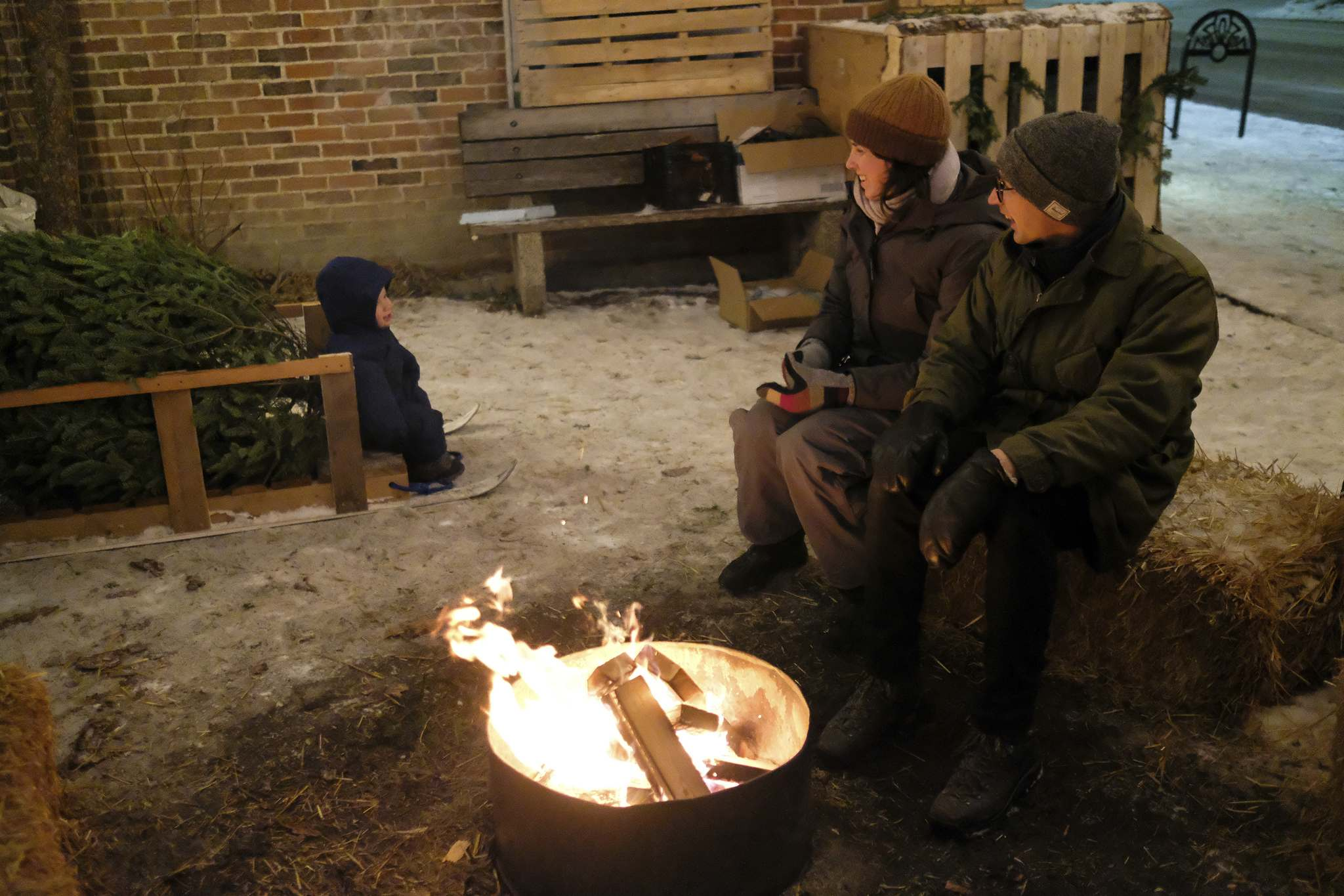 Conrad Petkau (right), Rebecca Beatty and their daughter, Evey, stay warm.</p>