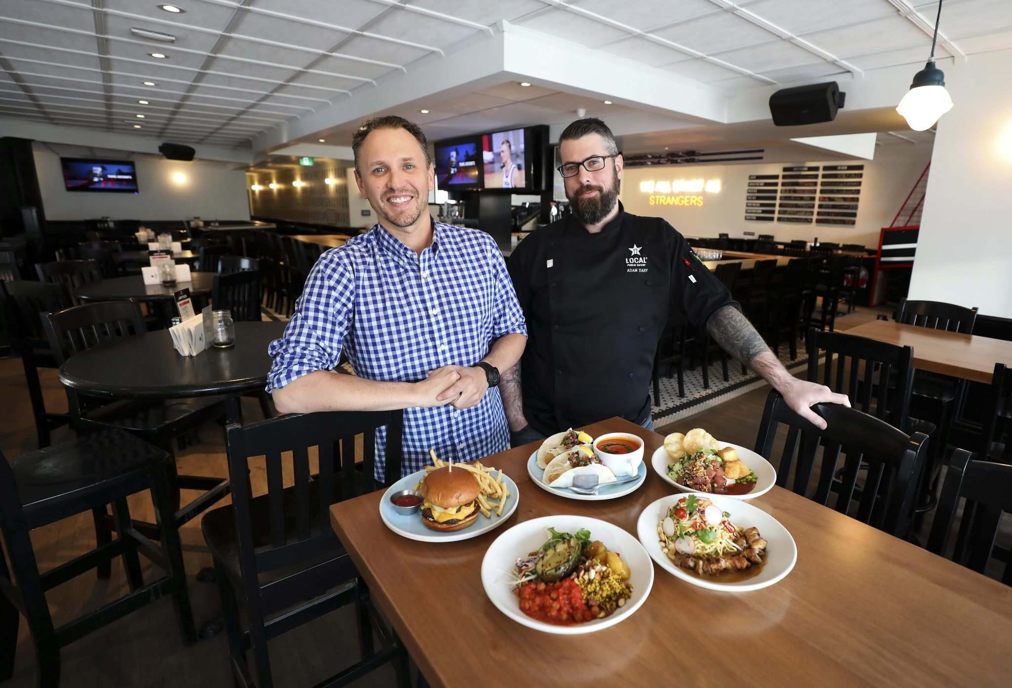 General Manager Sean Lough (left) with Chef Adam Dary and a selection of dishes including (from top left clockwise): Local burger, Mexican fish tacos with tomato soup, poke rice bowl, Thai noodle salad and power bowl. (Ruth Bonneville / Winnipeg Free Press)