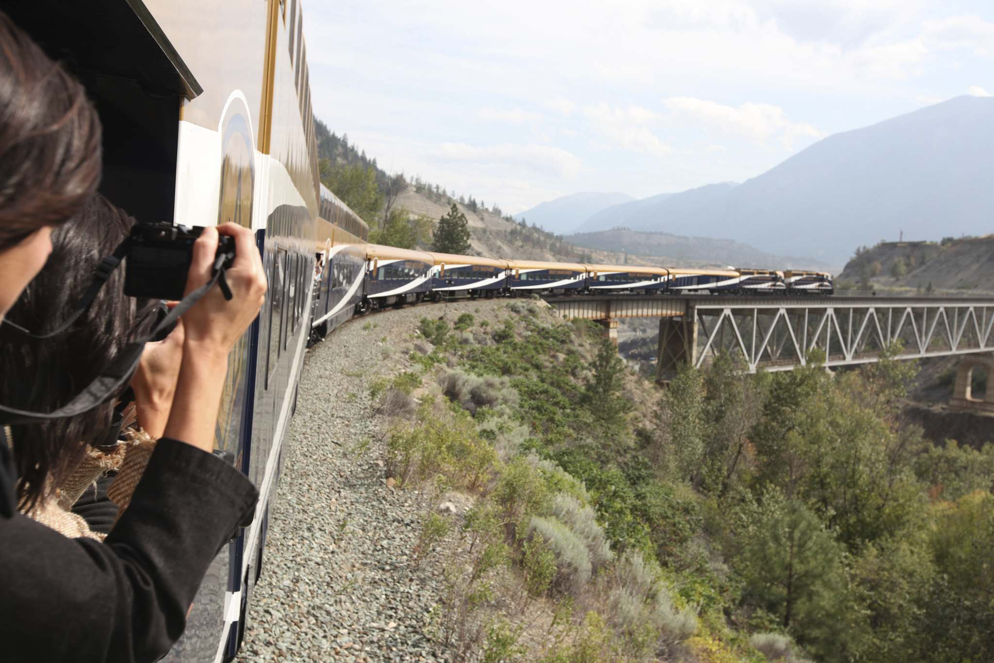 ROCKY MOUNTAINEER</p><p>Passengers on the Rocky Mountaineer take pictures from the open-air observation deck.</p></p>