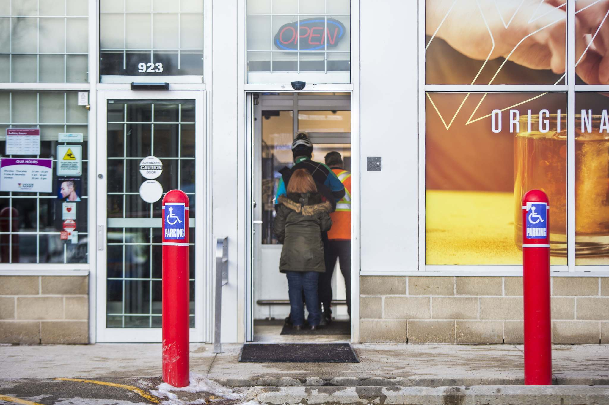 At the Portage Avenue and Burnell Street Liquor Mart, the transaction window is built into the glass wall of the entrance vestibule and security is inside the store at a station with closed-circuit monitors. (Mikaela MacKenzie / Winnipeg Free Press)