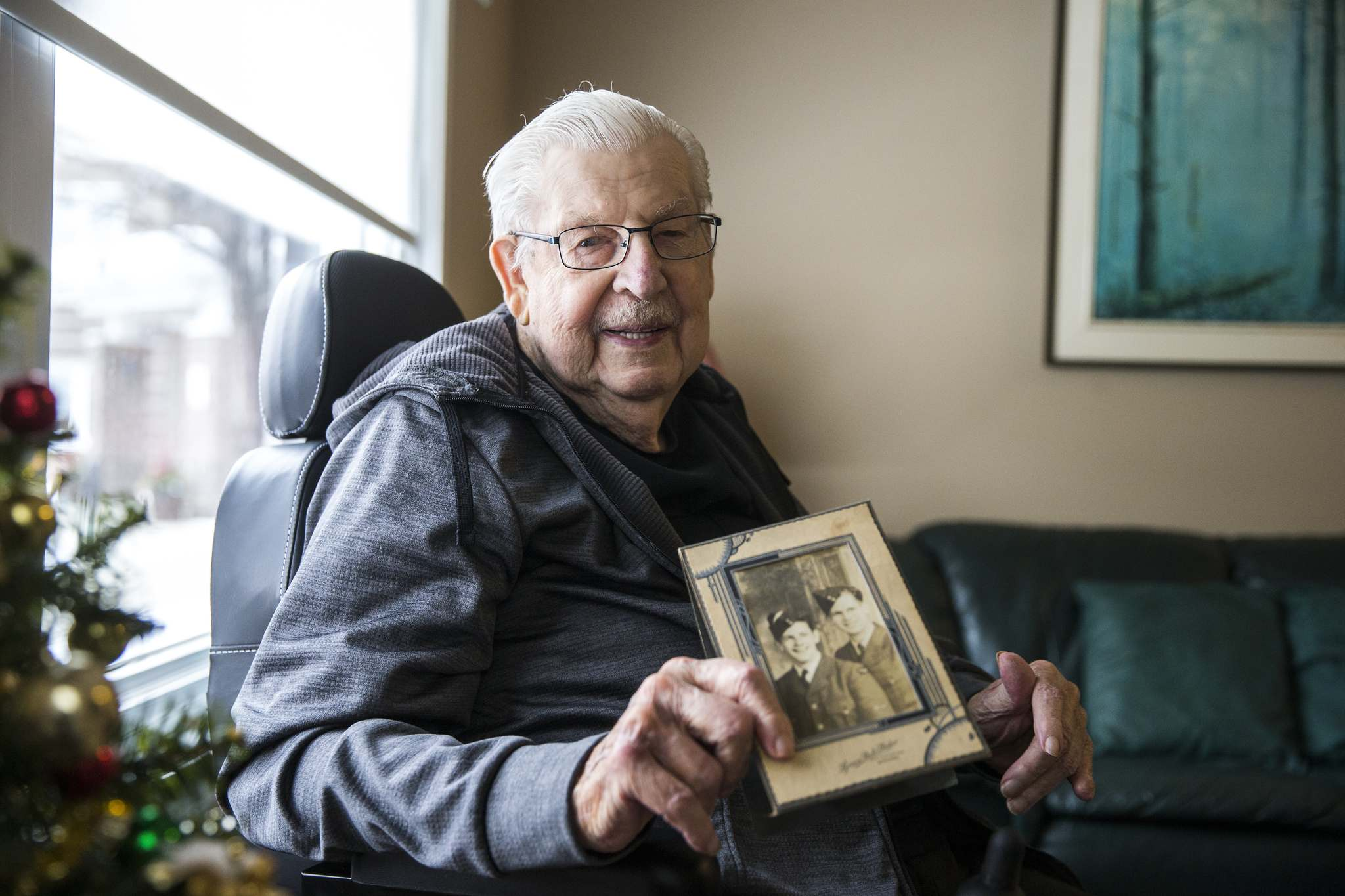 MIKAELA MACKENZIE / WINNIPEG FREE PRESS</p><p>Henry Golis, a 93-year-old Transcona resident who survived a plane crash in WWII, poses with a wartime photo of him (left) and his brother, Chester Golis, when the two were 17 and 22. Transcona's city councillor wants to give an honorary street name to a stretch of Regent Avenue for him.</p>