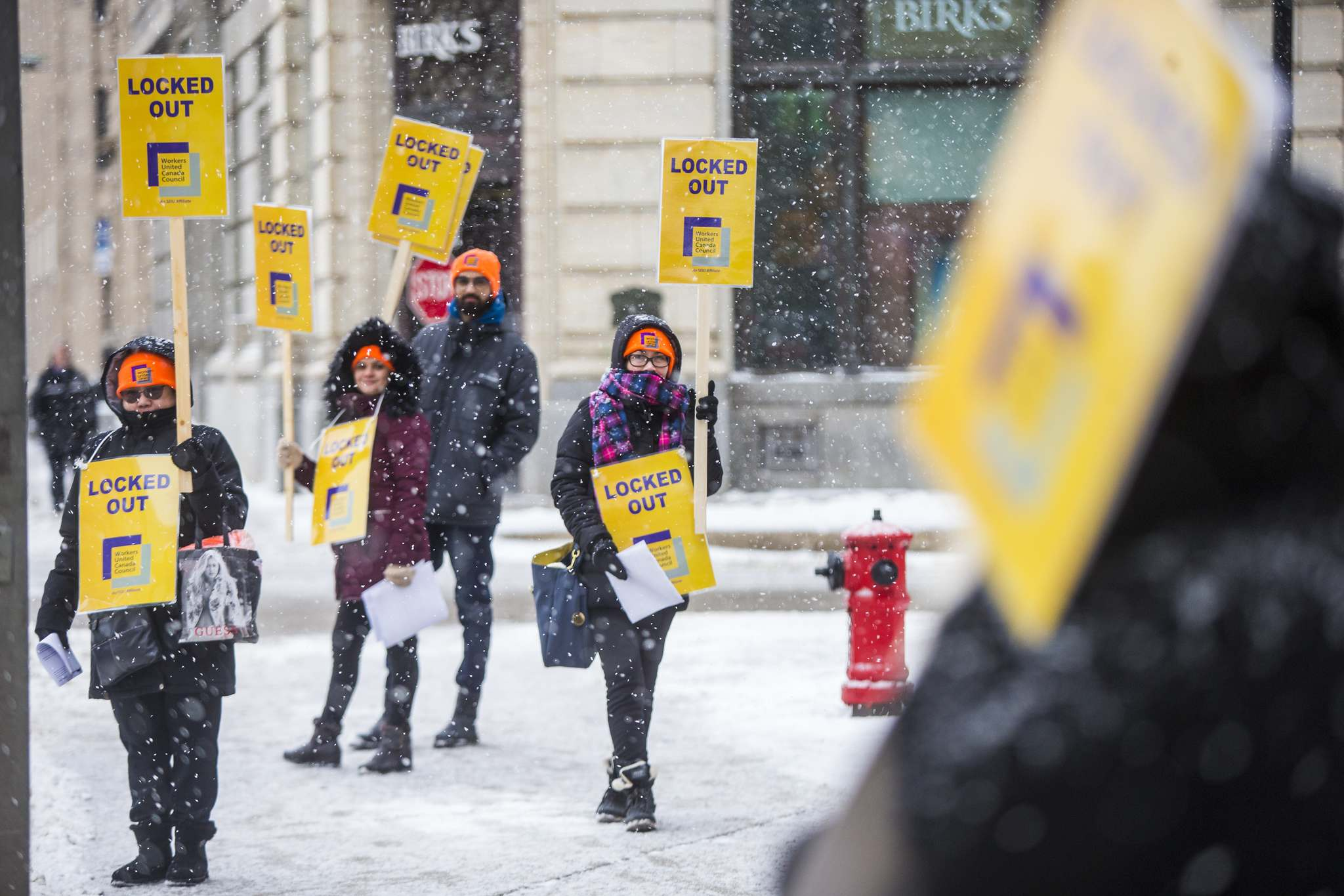 Cherry Garcia (centre) holds a sign at a rally of Tim Hortons employees outside of 1 Lombard Place on Friday. Fifteen workers at the restaurant were seeking a 30-cent increase in a recent round of collective bargaining. (Mikaela MacKenzie / Winnipeg Free Press)</p>