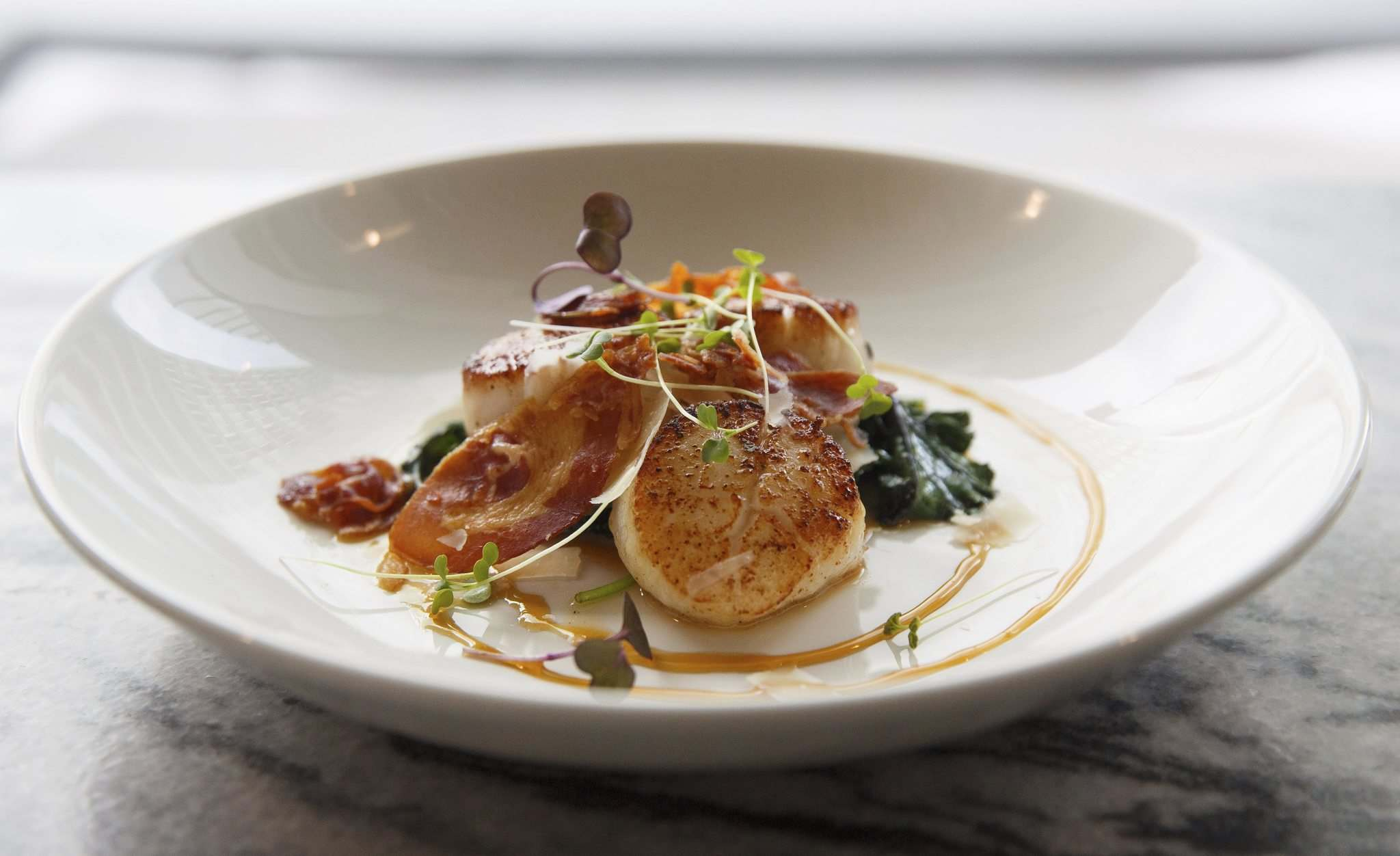 Scallops Pancetta with white balsamic, amaretto and winter greens.