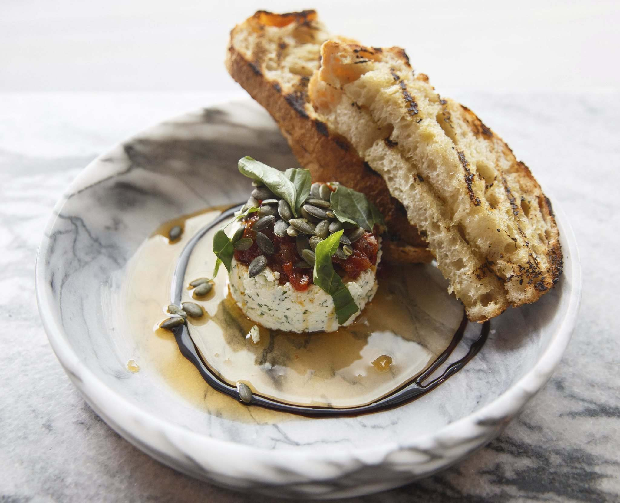 Ricotta Della Piazza San Mariano features tomato jam, chili oil, pumpkin seeds, basil and grilled sour dough.