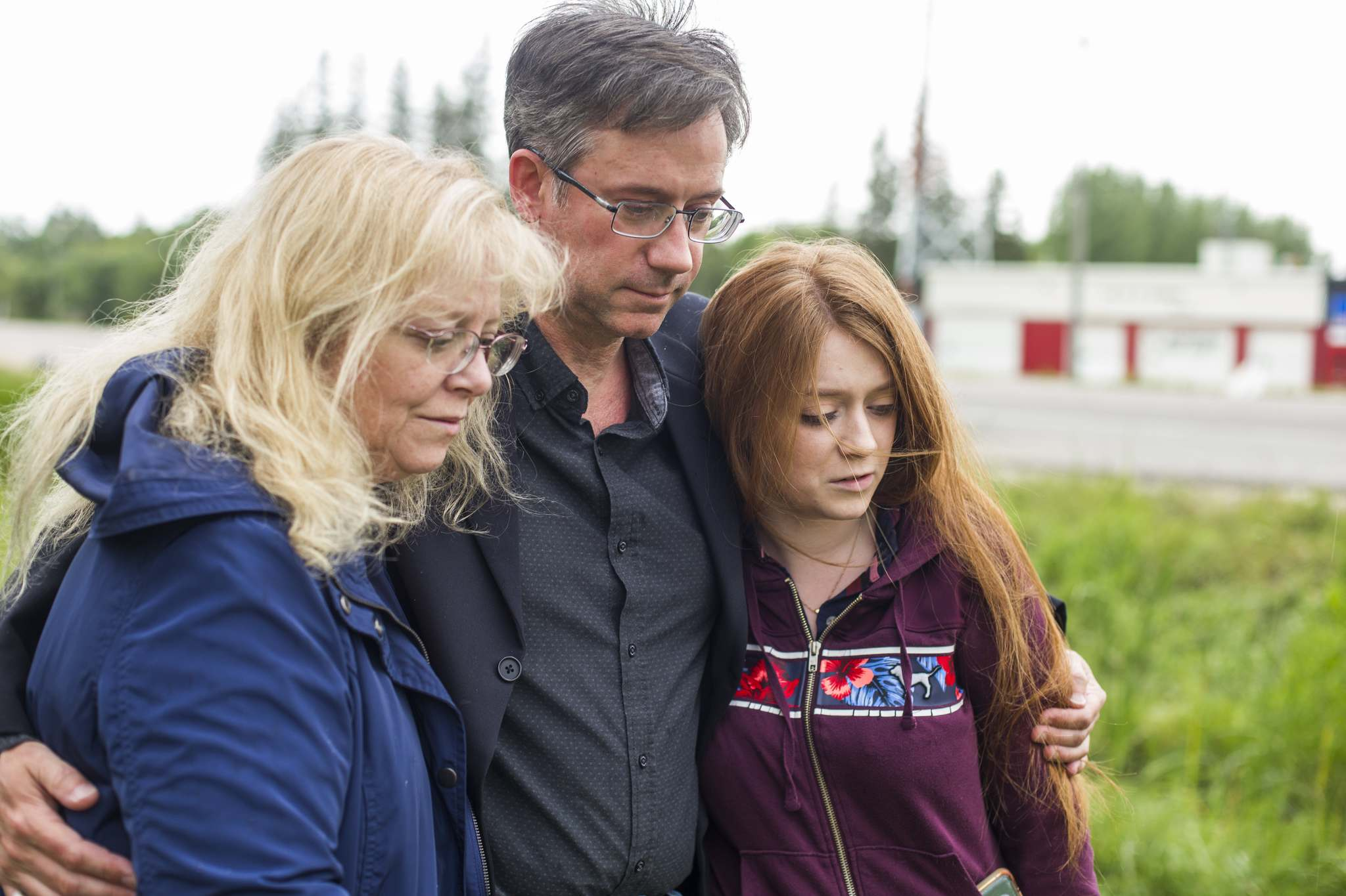 Brenda (left), John, and Hannah Harris stand by the makeshift memorial on Donald Road last August. (Mikaela MacKenzie / Winnipeg Free Press)
