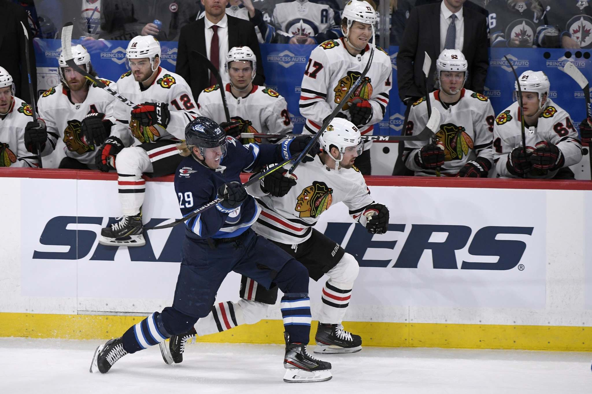 Winnipeg Jets' Patrik Laine (29) checks Chicago Blackhawks' Erik Gustafsson (56) in front of the Blackhawks bench during first period NHL action in Winnipeg on Sunday. Feb. 16, 2020. THE CANADIAN PRESS/Fred Greenslade</p>